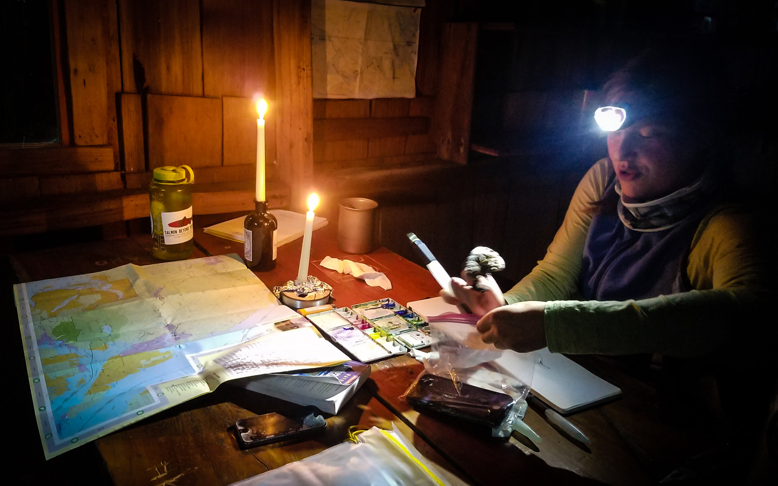 Mara illustrating by candle and headlamp