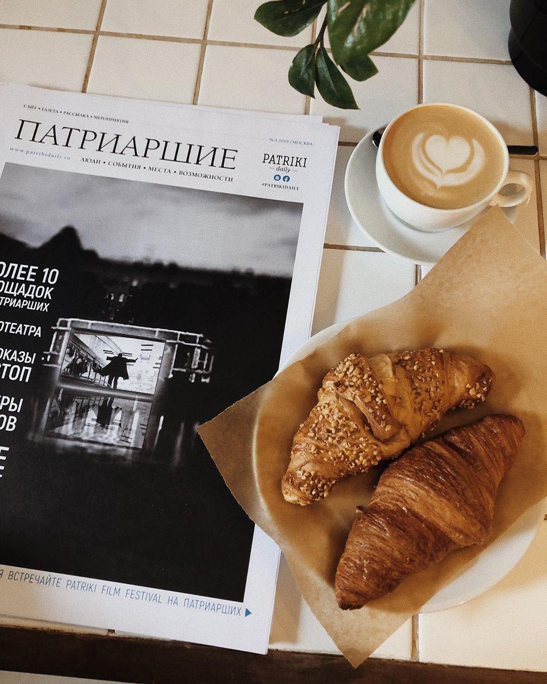 Латте, круассан и газета в кофейне David B. Café