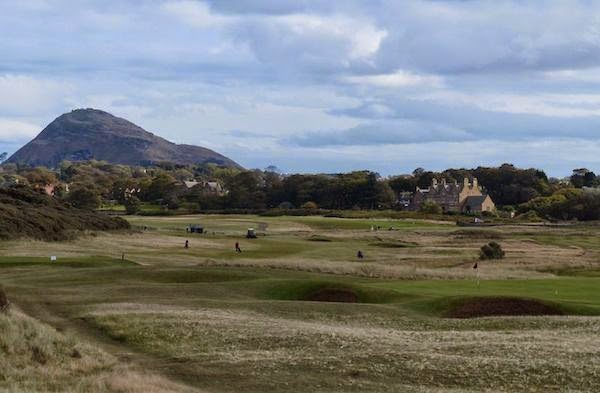 """The Pathway Home -- At the tee of the par 3 10th hole (Eastward Ho!), the course heads back to the clubhouse. The mini mountain in the background is called North Berwick's Law, which Wikipedia describes as a """"volcanic plug of hard phonolithic trachyte rock of Carboniferous (Dinathian) age."""" Easy for them to say."""