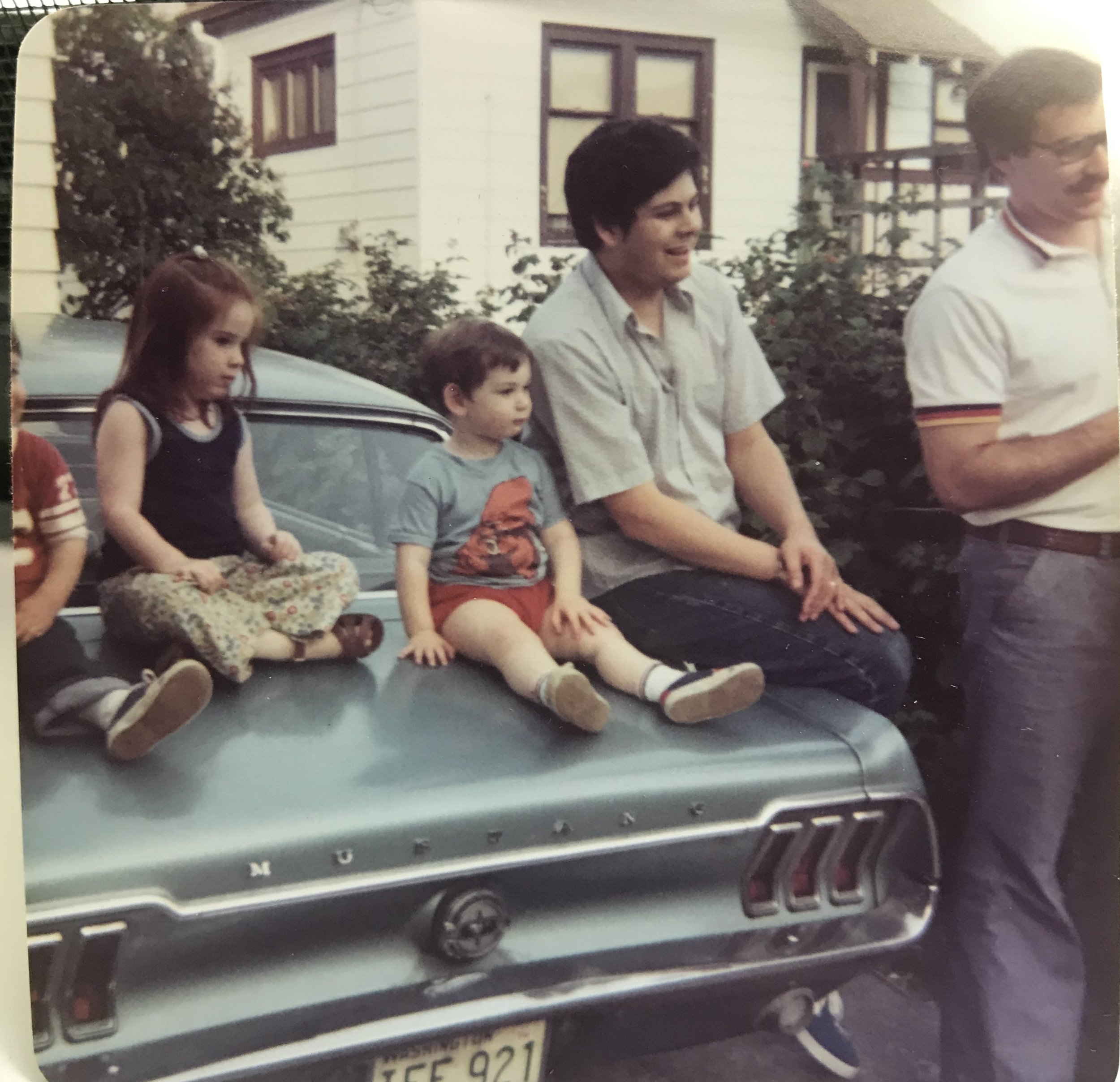 This must be summer of 1975 so I'm 4, almost 5 years old - that's me with the red hair on our blue mustang we had when I was small. We'd slide around the back seat - omg the safety back then was so bad - you can see how short my arms next to my cousin who must be barely 2 years old. My brother is to my right, then two uncles on the end. I think it was 4th of July, I don't know why I remember that but look how serious I am while everyone else is smiling. I was a very, very serious kid.