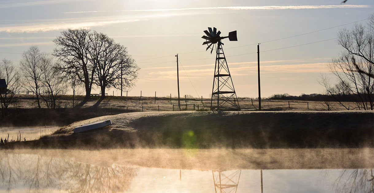 On a cold day at the farm,steam rises off the pond.