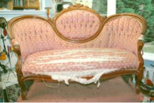 This settee frame was repaired and re-glued. The show wood was cleaned and polished. The padding was re-worked and freshened. The tufting in the center was retained and the wings were altered to a smooth pulled finish.