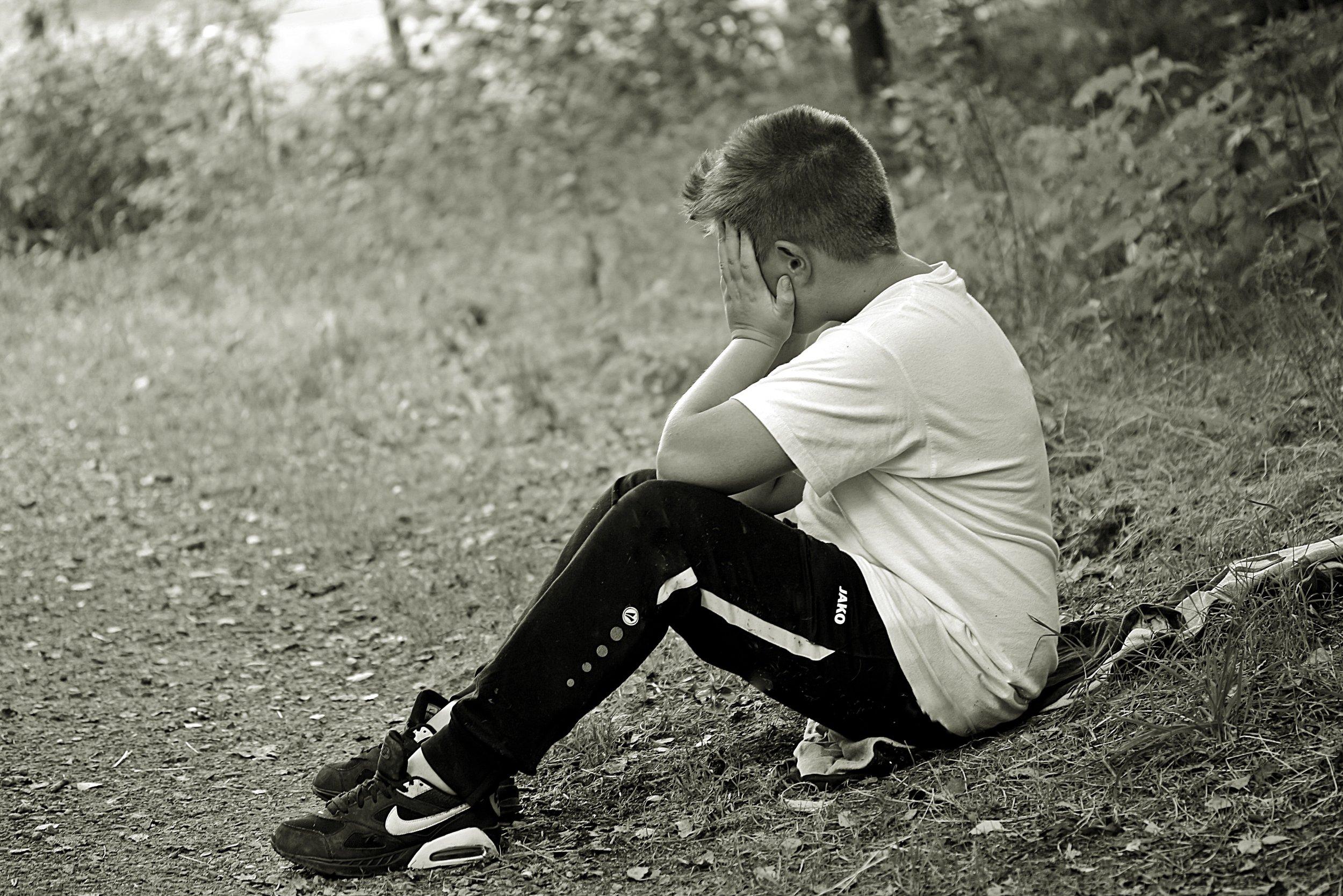 boy-profile-hiding-face-sitting-knees-bent-black-white.jpg