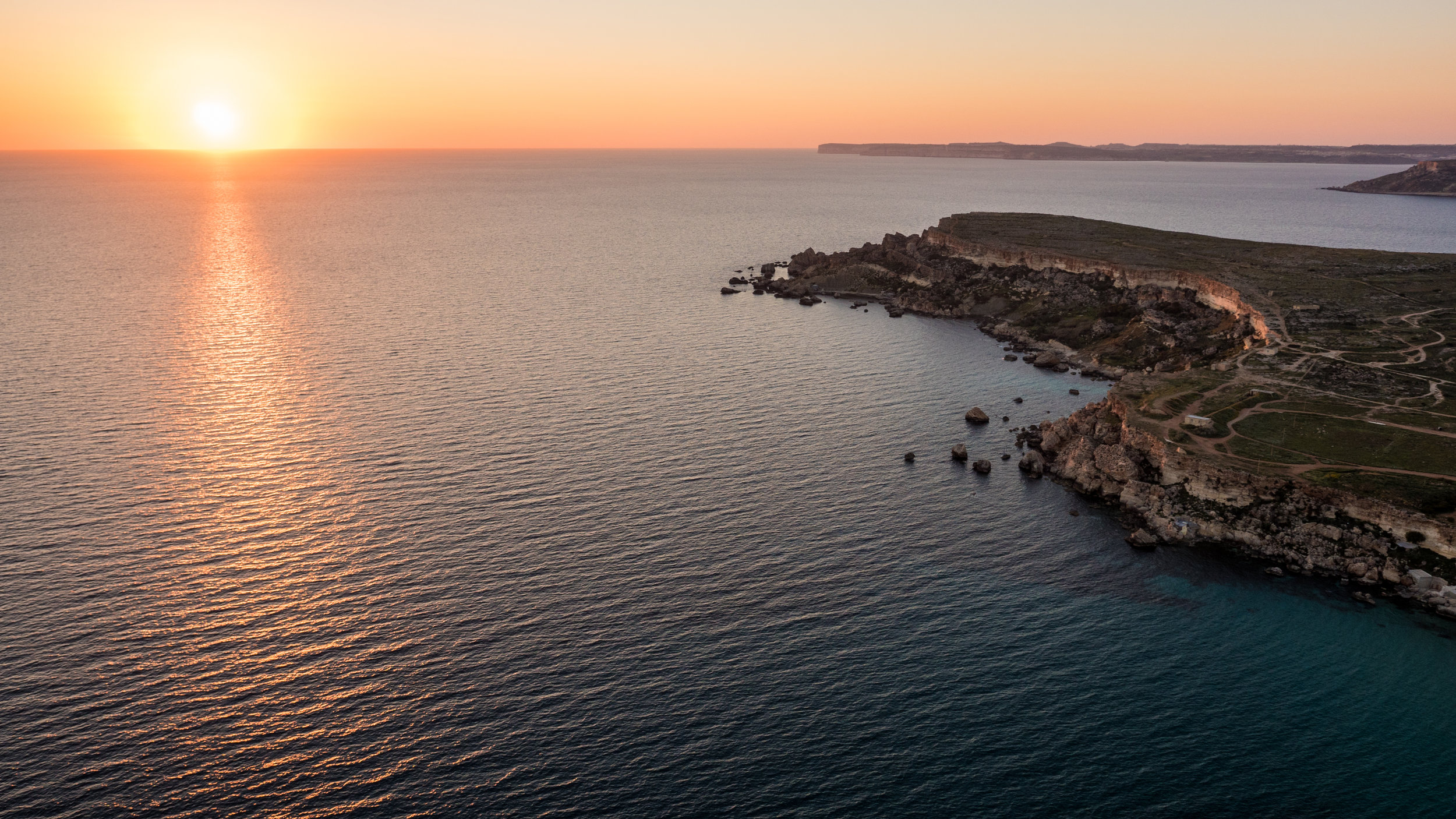 Aerial view of sunset on Golden Bay, Malta, one of my favourite sunset viewing points on the island