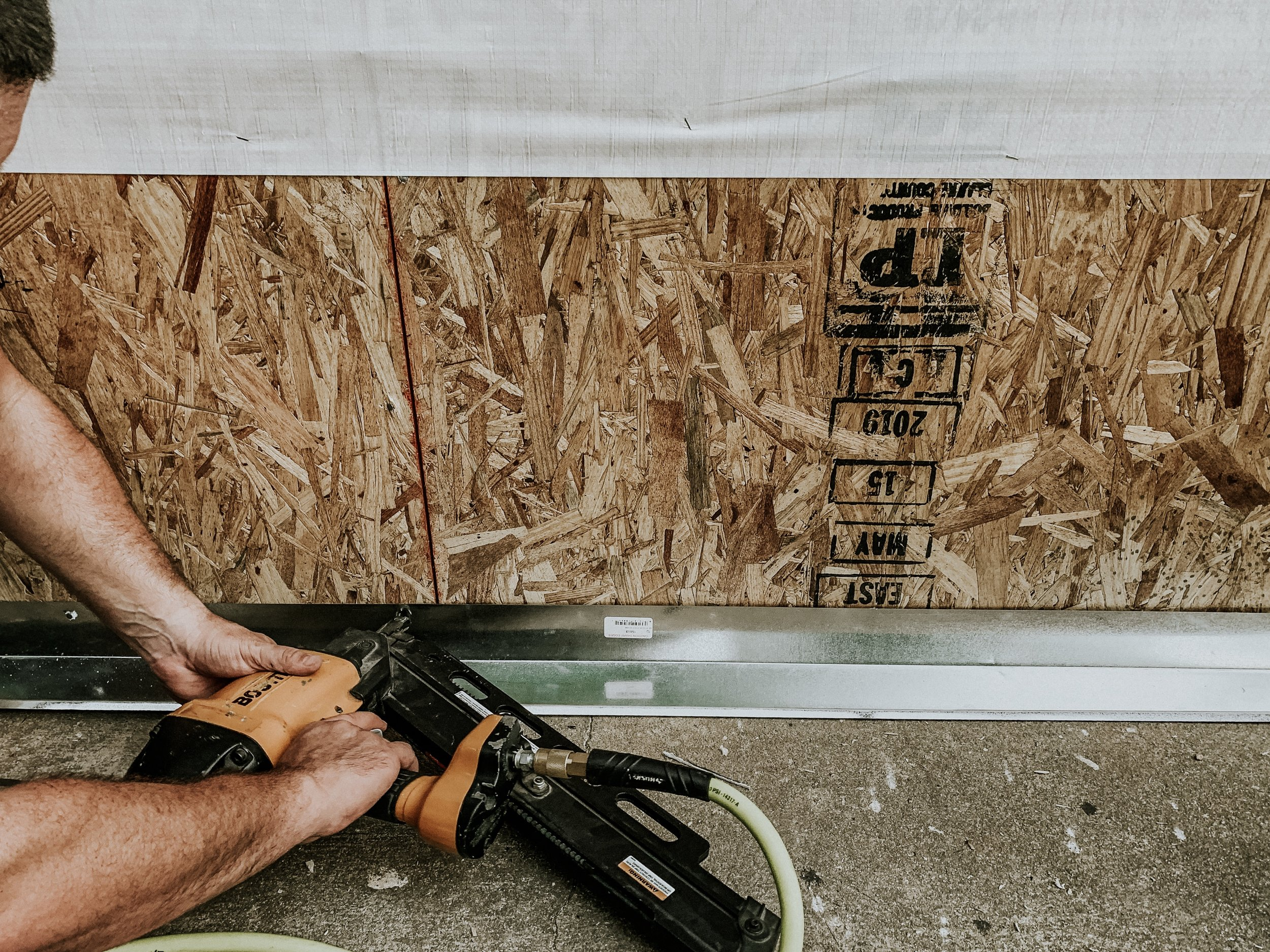 Attaching drip edge flashing to a plywood wall