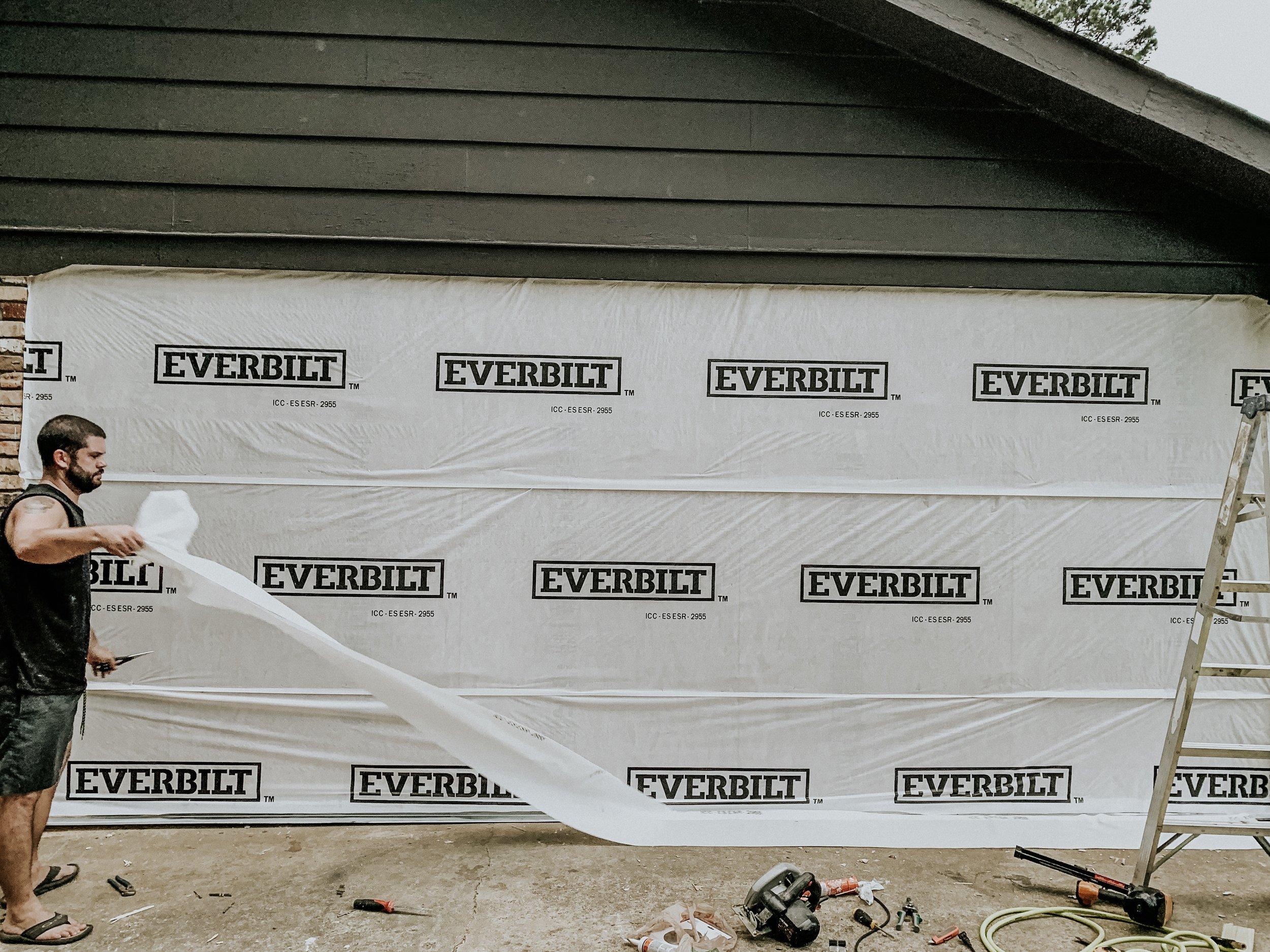 Applying Everbilt water vapor barrier to exterior of home