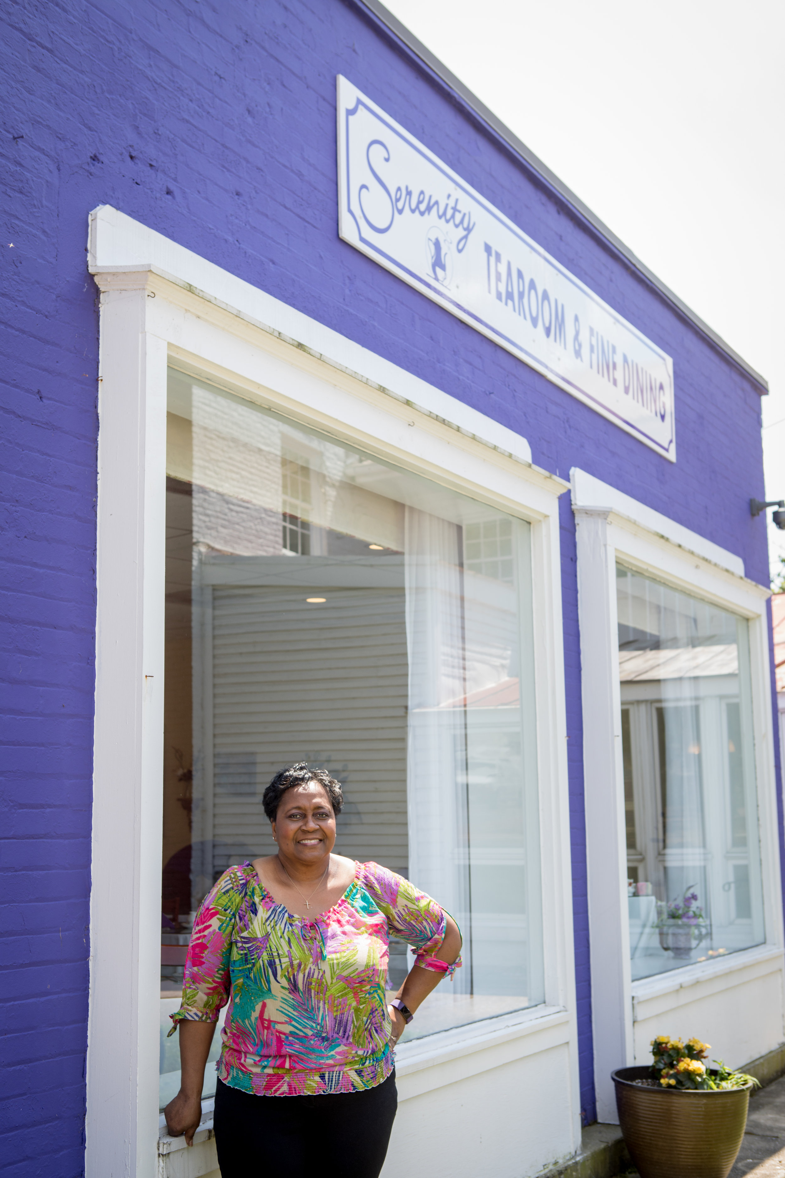 Blanch Henry shows off the purple exterior paint on Serenity Tearoom & Fine Dining.