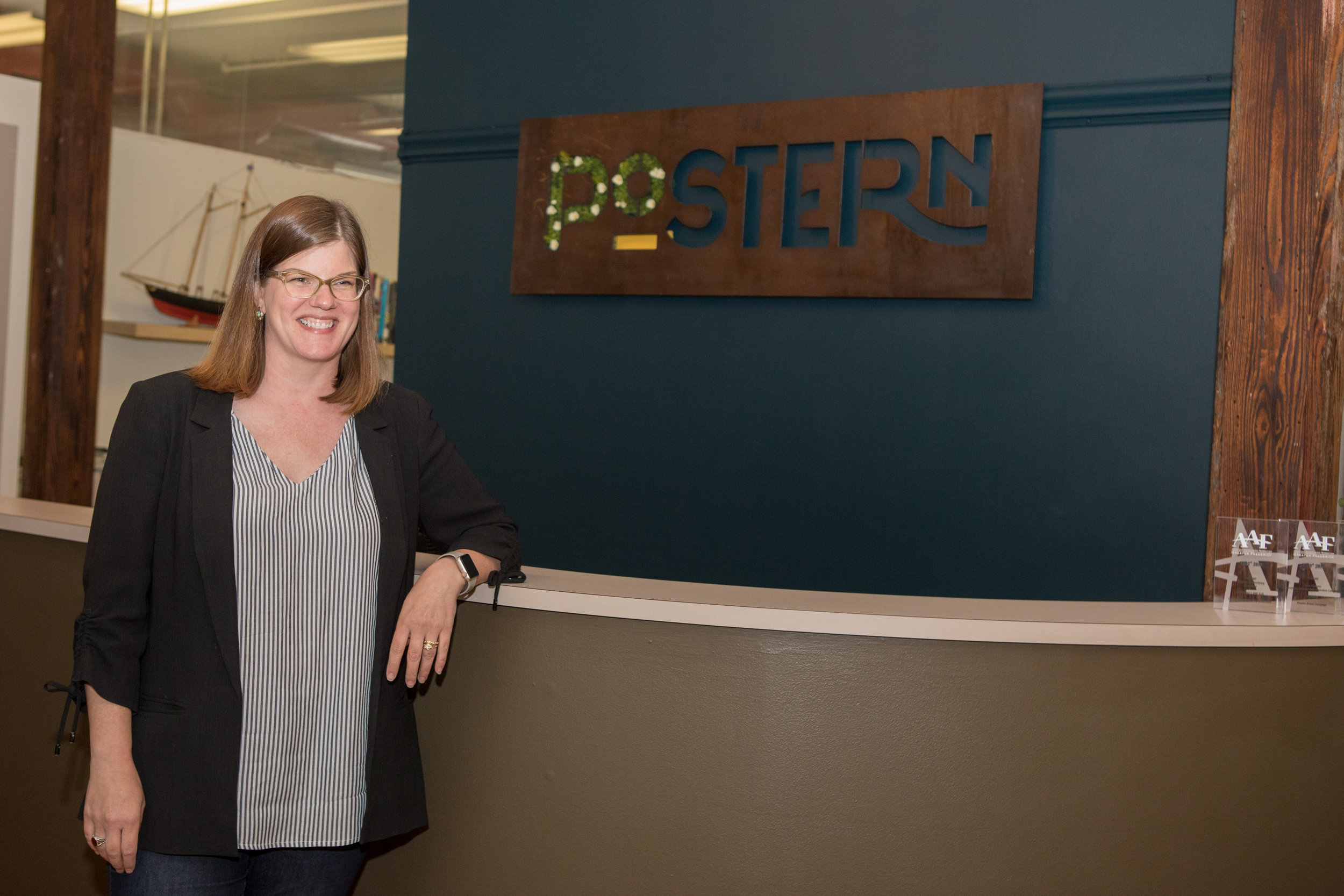 Emily Dorr poses next to the Postern Agency sign.