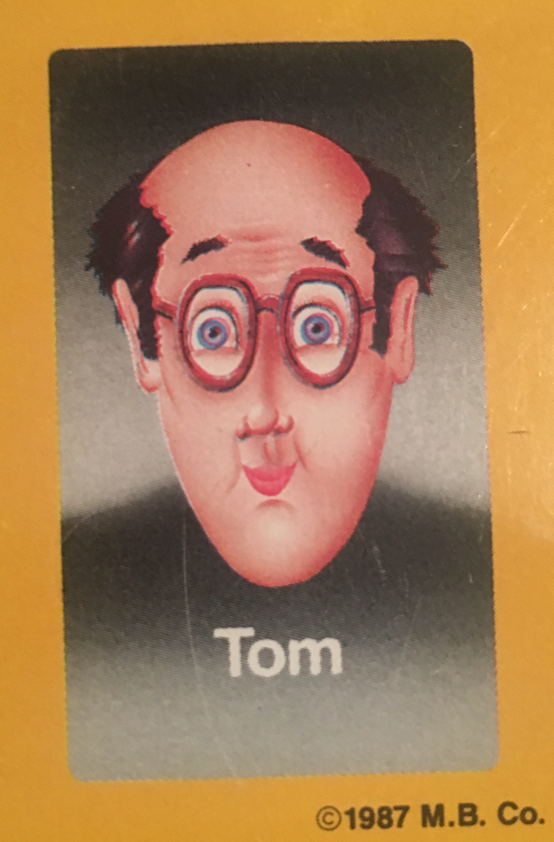 - Tom was always a game enthusiast, which is what landed him the gig as a Guess Who?® face in the first place; he was at Milton Bradley headquarters to protest the newly released Hungry Hungry Hippos game, as he had been injured during some particularly intense gameplay the night before. They offered him a Guess Who?® game card position in exchange for his silence, and he enthusiastically accepted. In the years since, he has gone into semi-retirement, spending most of his time on the Magic: The Gathering Pro Tour.