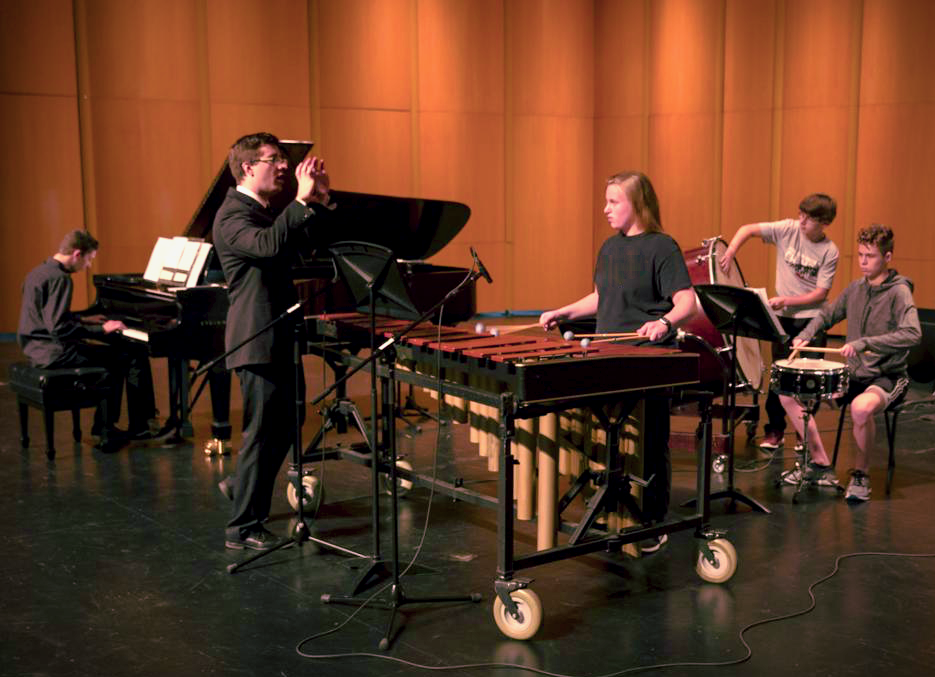 """""""Jon Nelson, second from left, talks to composer and pianist, Ryan Sellek, Bella Wineke, Jonathan Foster, Griffin Langhan, all 9th graders, and Jacob Couch, 11th grade, during a rehearsal of Resonance 2018 at the Sun Prairie Performing Arts Center. Sellek's composition is titled, """"The Sunken Meadows March.""""  ANDY MANIS, FOR THE STATE JOURNAL""""   (Source: Wisconsin State Journal)"""