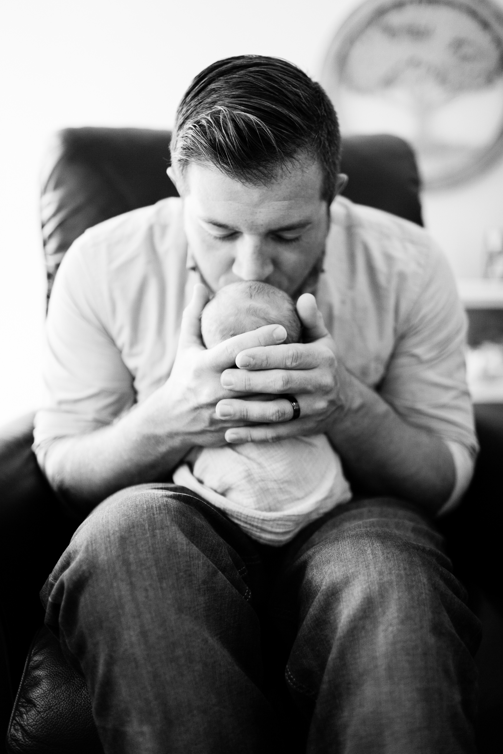 black and white dad kissing newborn