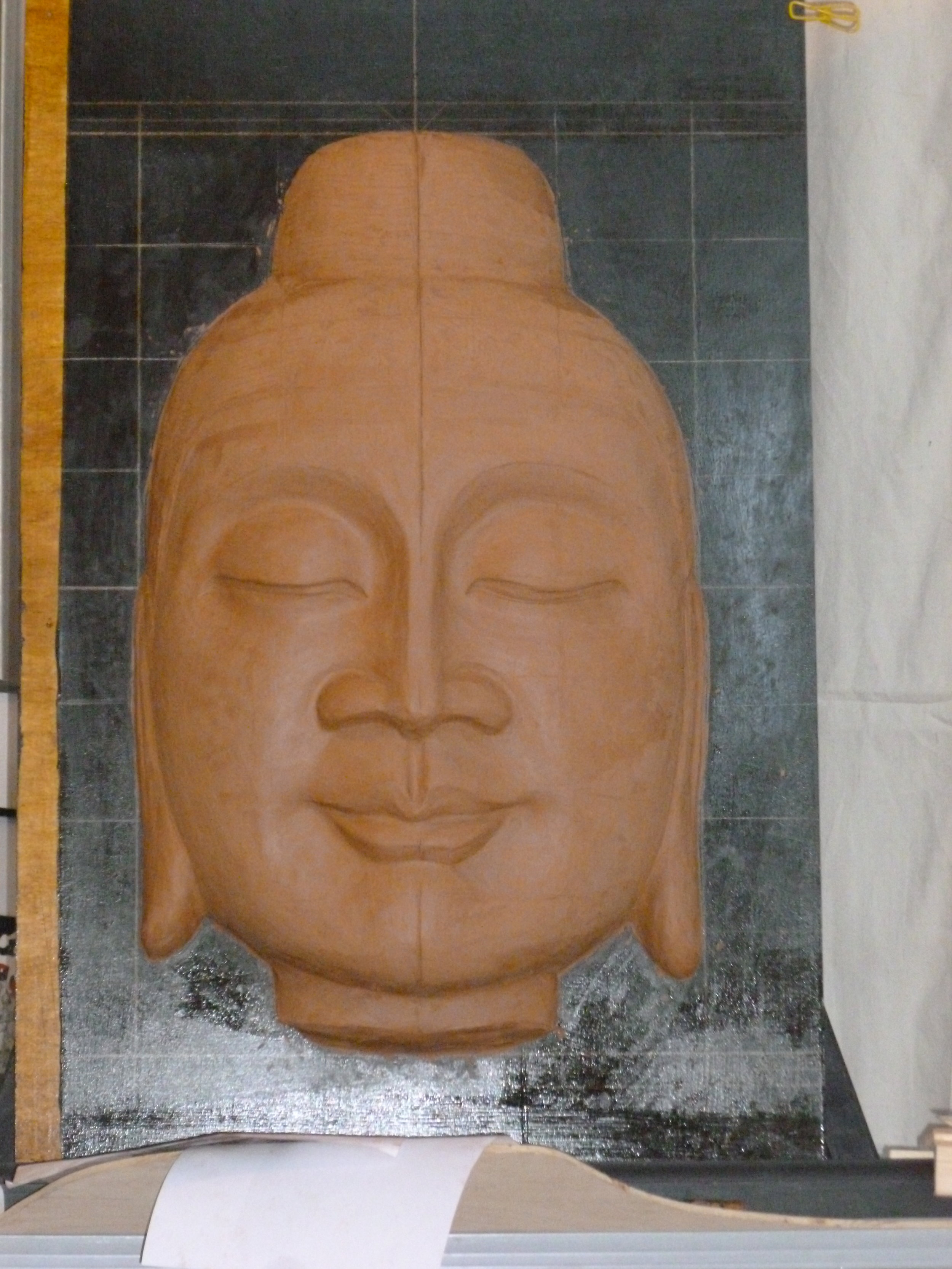 Sculpting the clay model for the  Fountain Buddha.  The grid is used for assessing symmetry.