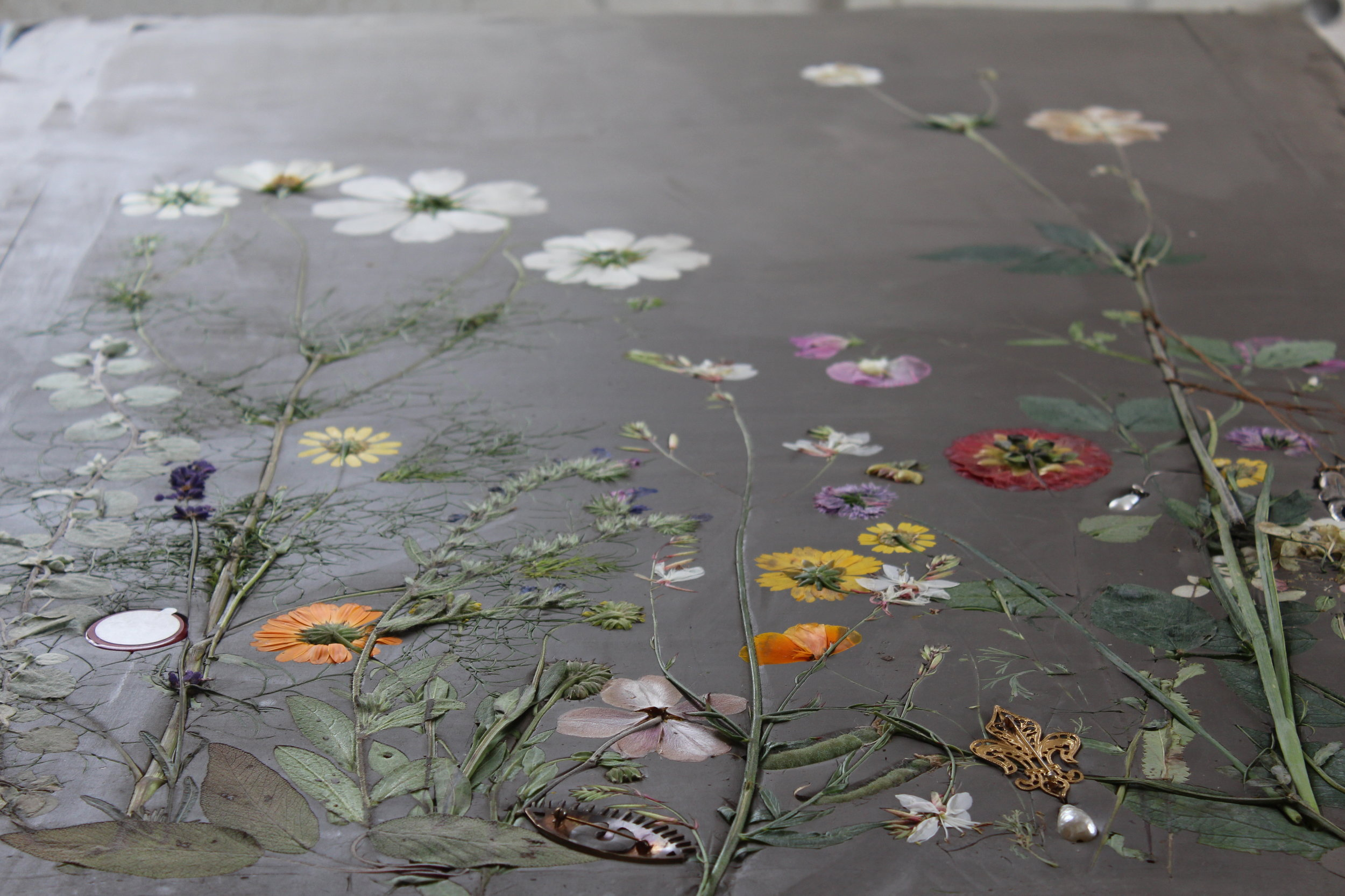 """Pressing flowers into a bed of clay to create a single-use mold, also known as a """"waste mold."""" Photo courtesy of the artist."""