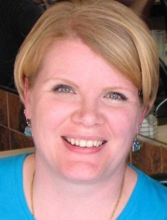 A headshot of a blonde woman smiling with blue earrings.