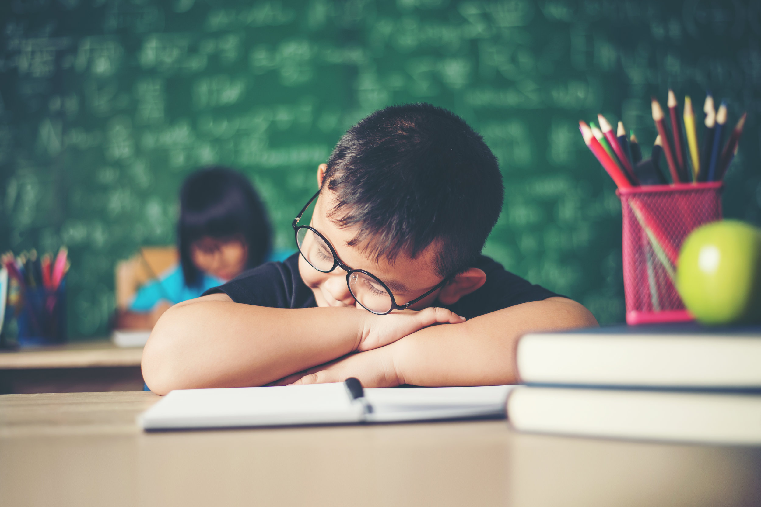 Boy_sleeping_on_the_books_in_the_classroom..jpeg