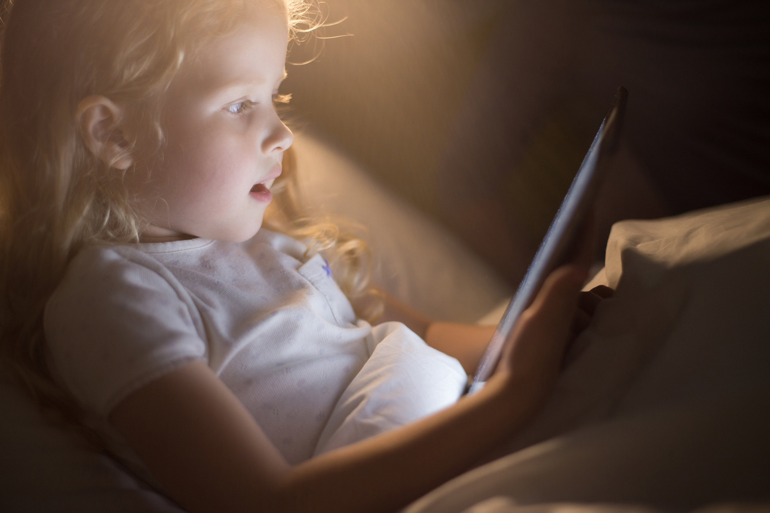 Side_view_portrait_of_adorable_little_girl_looking_amazed_with_mouth_open_using_digital_tablet_lying_in_bed_at_night,_face_lit_by_screen_light_like_magic,_copy_space.jpeg