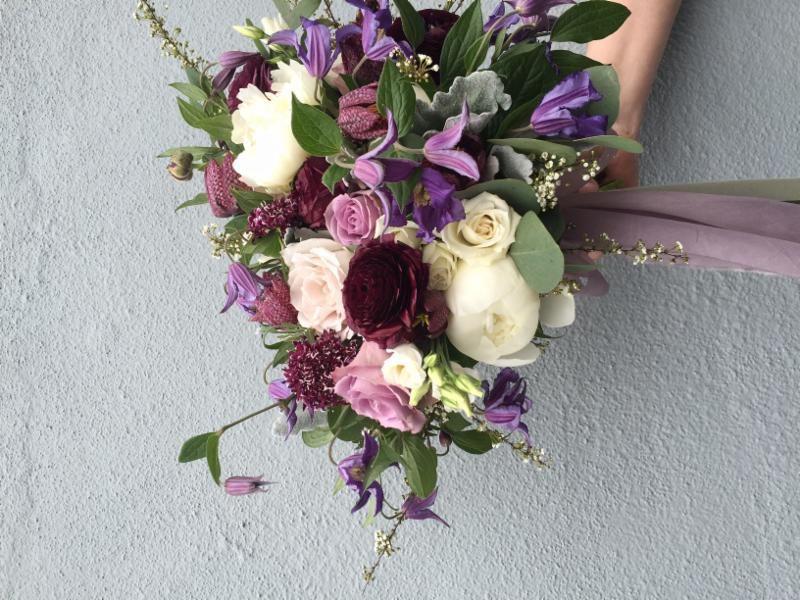 Rich, jewel-toned blooms blended with cream-coloured peonies and natural greenery carry an air of vibrant sophistication and elegance. Thorn & Thistle photo.