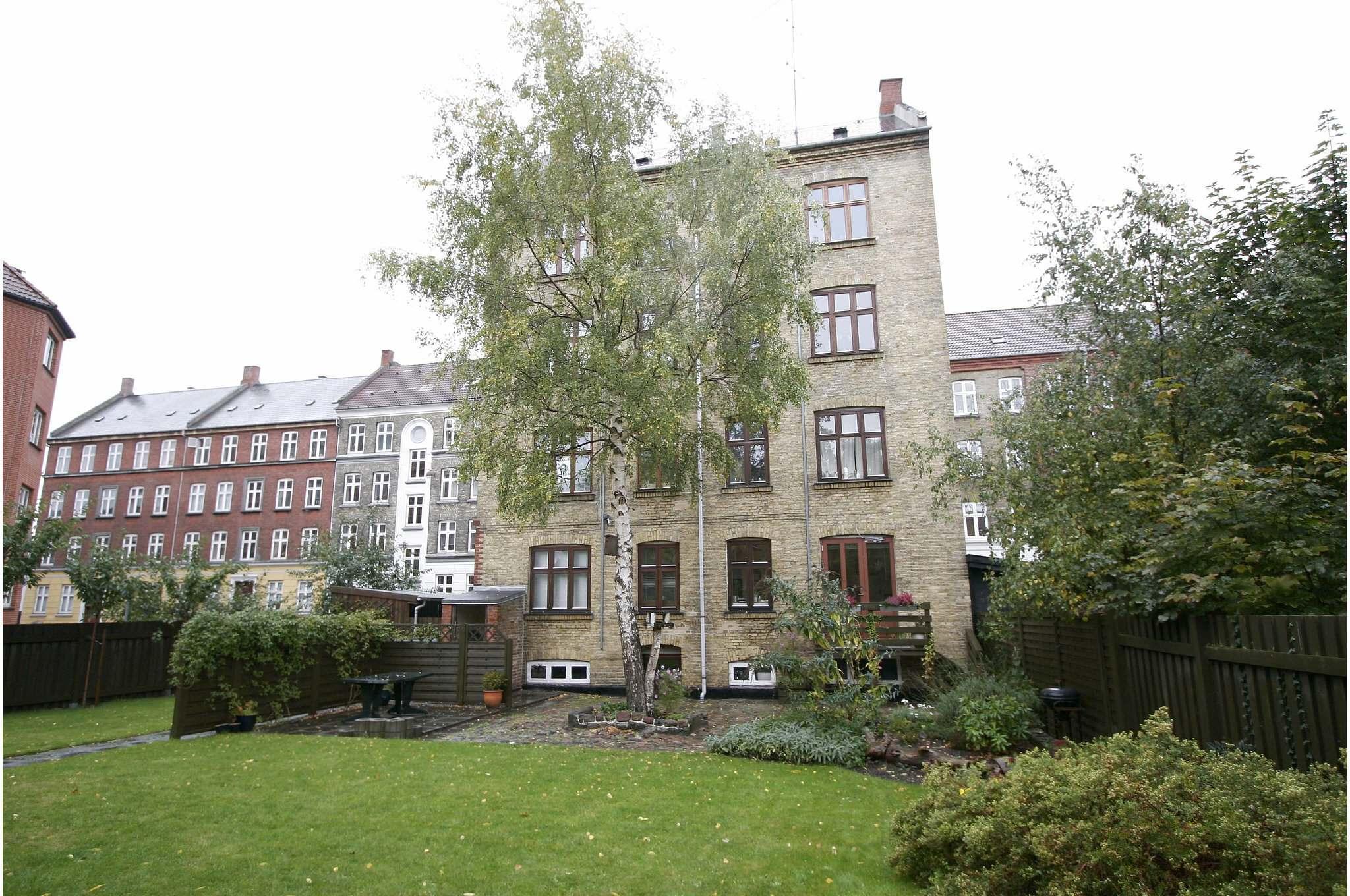 Huset set fra haven   Lejligheden er oprindelig en 2-værelses på ca. 45 m2 med et mindre køkken og soveværelse vent mod haven. Stuen mod gaden. Efter ombygning flyttes soveværelse mod gaden og der skabes et stort køkken/opholdsrum mod haven ved nedtagning af væg.