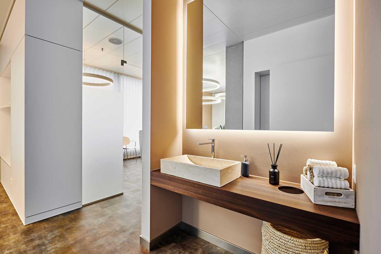 Abgeschirmte Beauty- Ecke mit warmweisser indirekter Beleuchtung, zusätzlich unterstützt durch den Erdton der Wand, ergibt eine angenehme und blendfreie Ausleuchtung des Bereichs.