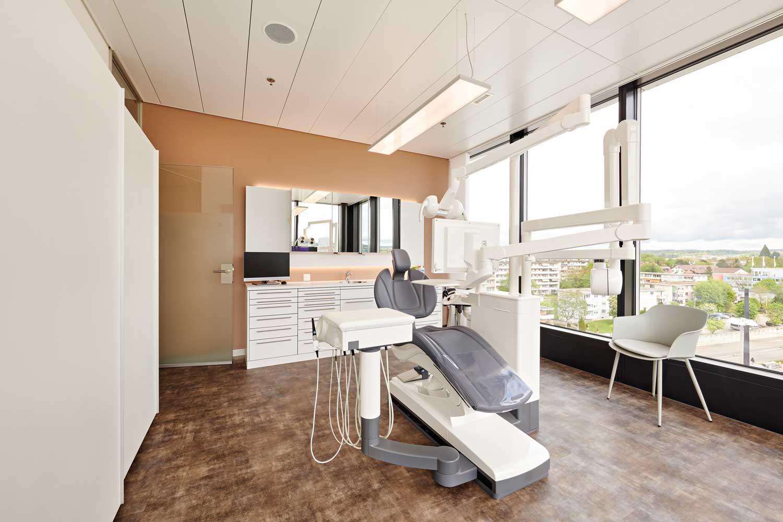 Alle Behandlungszimmer haben einen freien Blick auf die Umgebung. Die kaltweisse Beleuchtung des Zimmers verbindet sich optimal mit dem noch kühleren Tageslicht des Aussenraums.