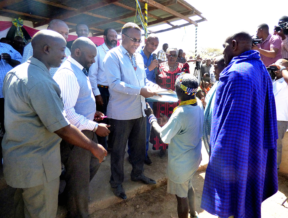 Caption: The Honorable Minister William Lukuvi handing over village land titles and CCROs (Certificate of Customary Right of Occupancy) to the Hadza and Datoga