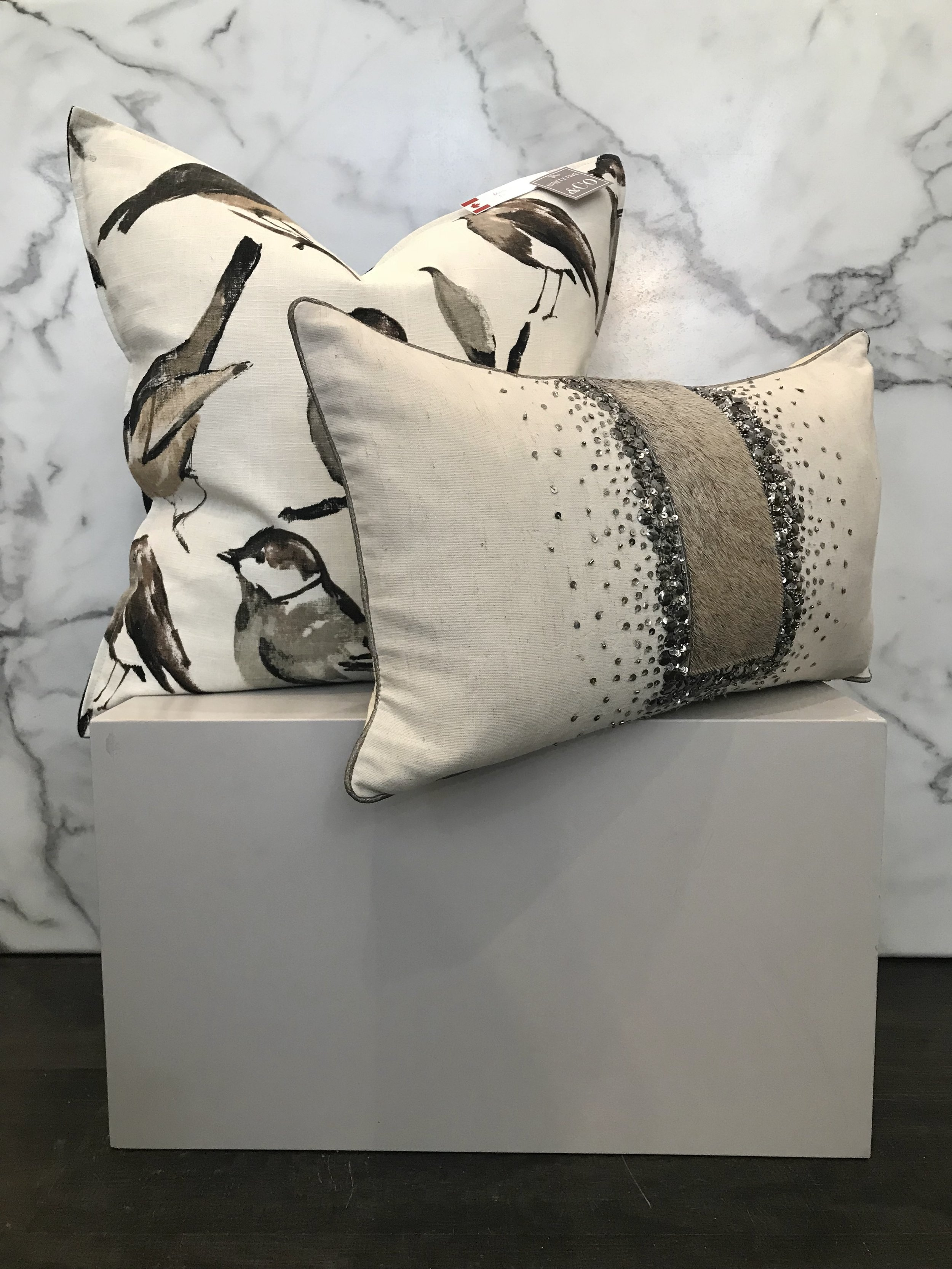 - Beautiful neutral pillows with bold and interesting prints and patterns can be a great choice for many homes. This over scale bird print is a great whimsical way to add some interest to any room while the cowhide pillow add some elegance and glam.