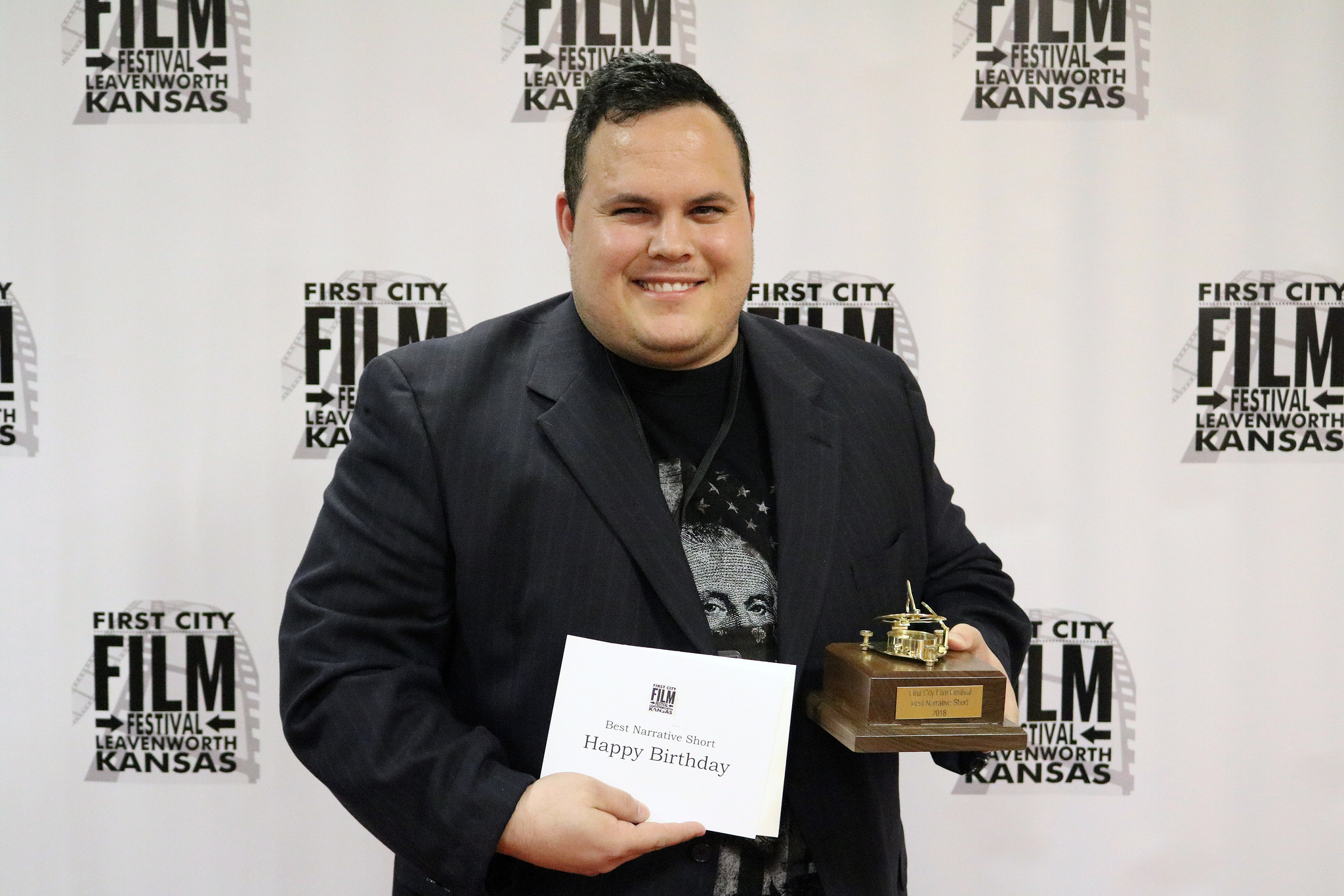 """- Filmmaker Kyle Kelley pauses for a photo during the award ceremony March 23, 2018 at the Riverfront Community Center in Leavenworth, Kan. Kelley's film """"Happy Birthday"""" received five awards at the 2018 festival including best narrative short, best local film, best film editing, best actor and best local supporting actress."""