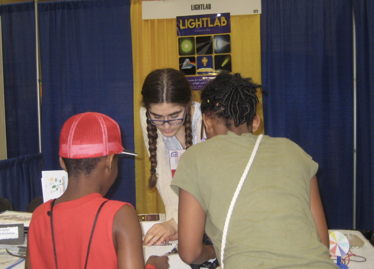 Miriam assisting two attendants at CHAP (Christian Homeschool Association of PA).