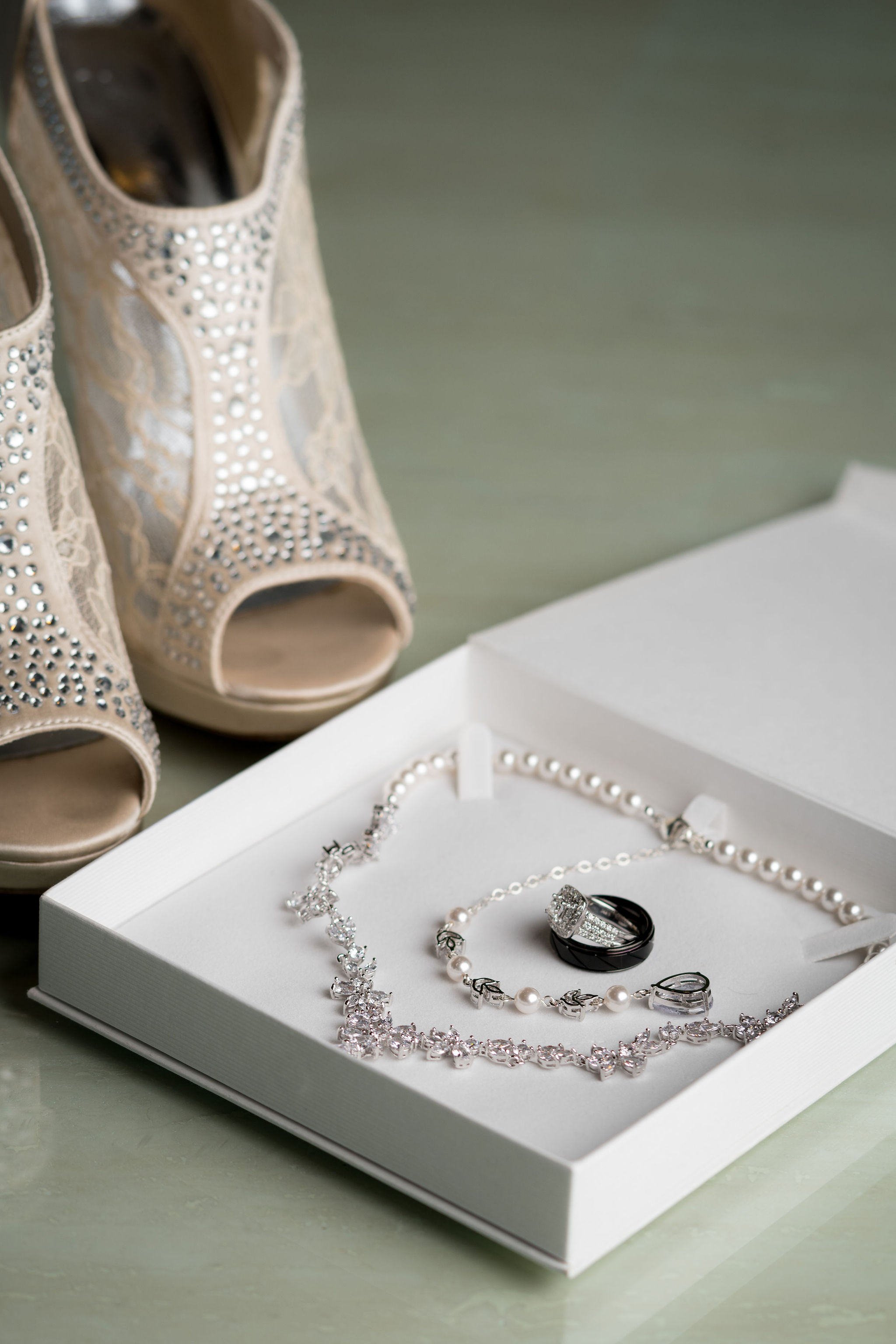 Bride's wedding ring, shoes and necklace at Sand Creek Country Club.