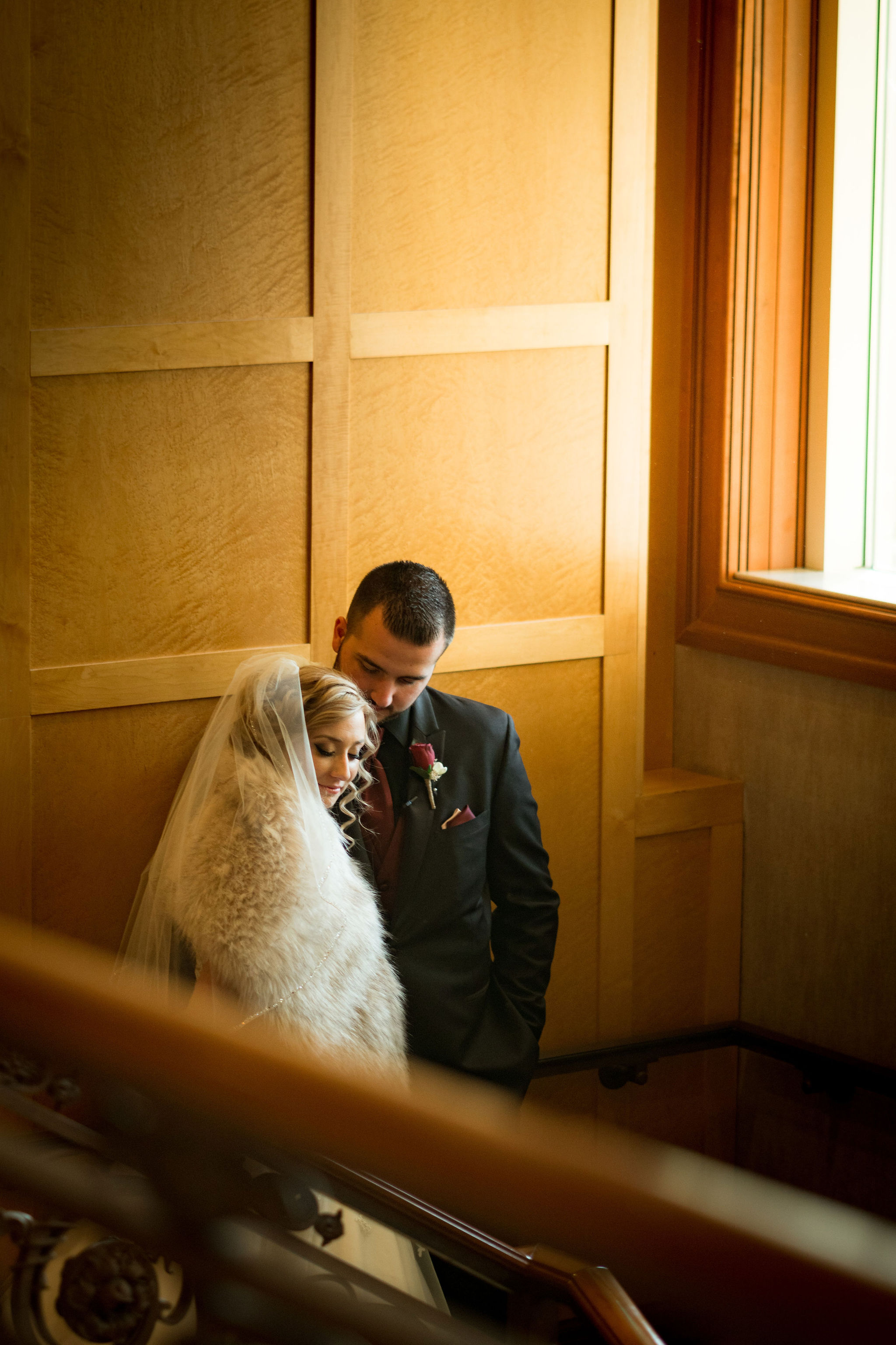 Artistic wedding portrait against wooden wall at Sand Creek Country Club.