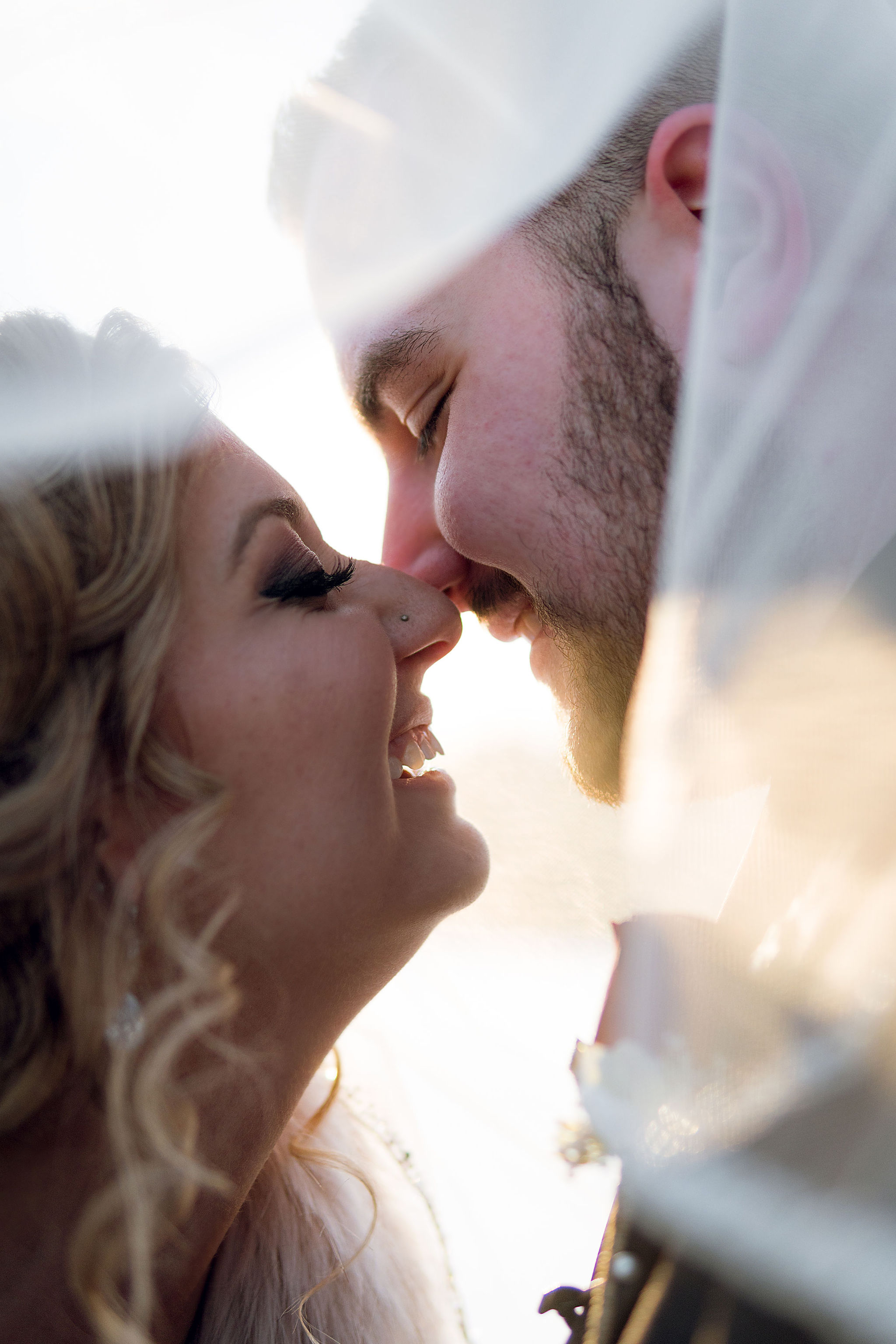 Romantic kiss during sunset bridal portrait at Sand Creek country club.