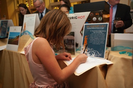 Young girl in pink dress fills out a silent auction form at the 2017 Visionary Gala.