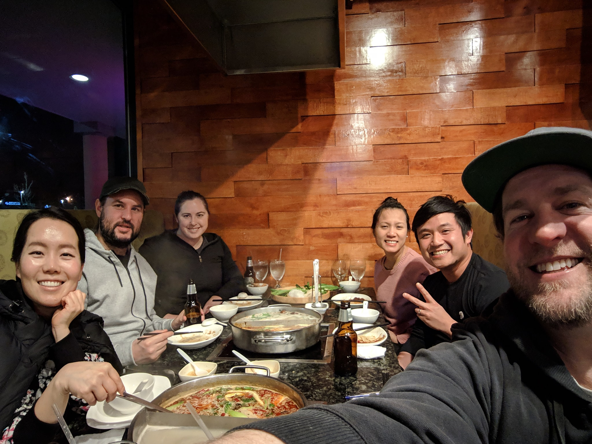 Lucas, Tuan, Nick and their partners sharing a meal at a Chinese Hot Pot restaurant.