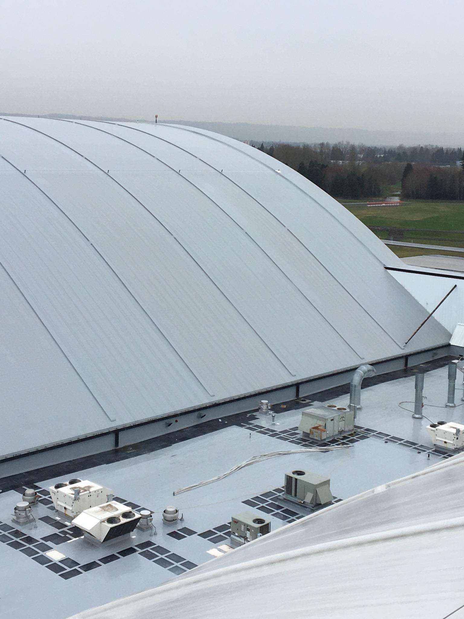 Horizontal lifeline on a barrel roof of a paint hangar for aerospace.