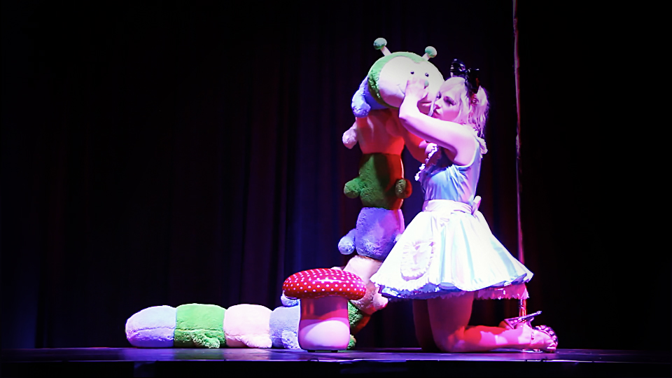 Alice & The Caterpillar - An act full of whimsy leading to transformation twist at the end. This award winning act features a giant 8ft long soft toy caterpillar and a combo pole and burlesque act.(Can be performed with or without pole)