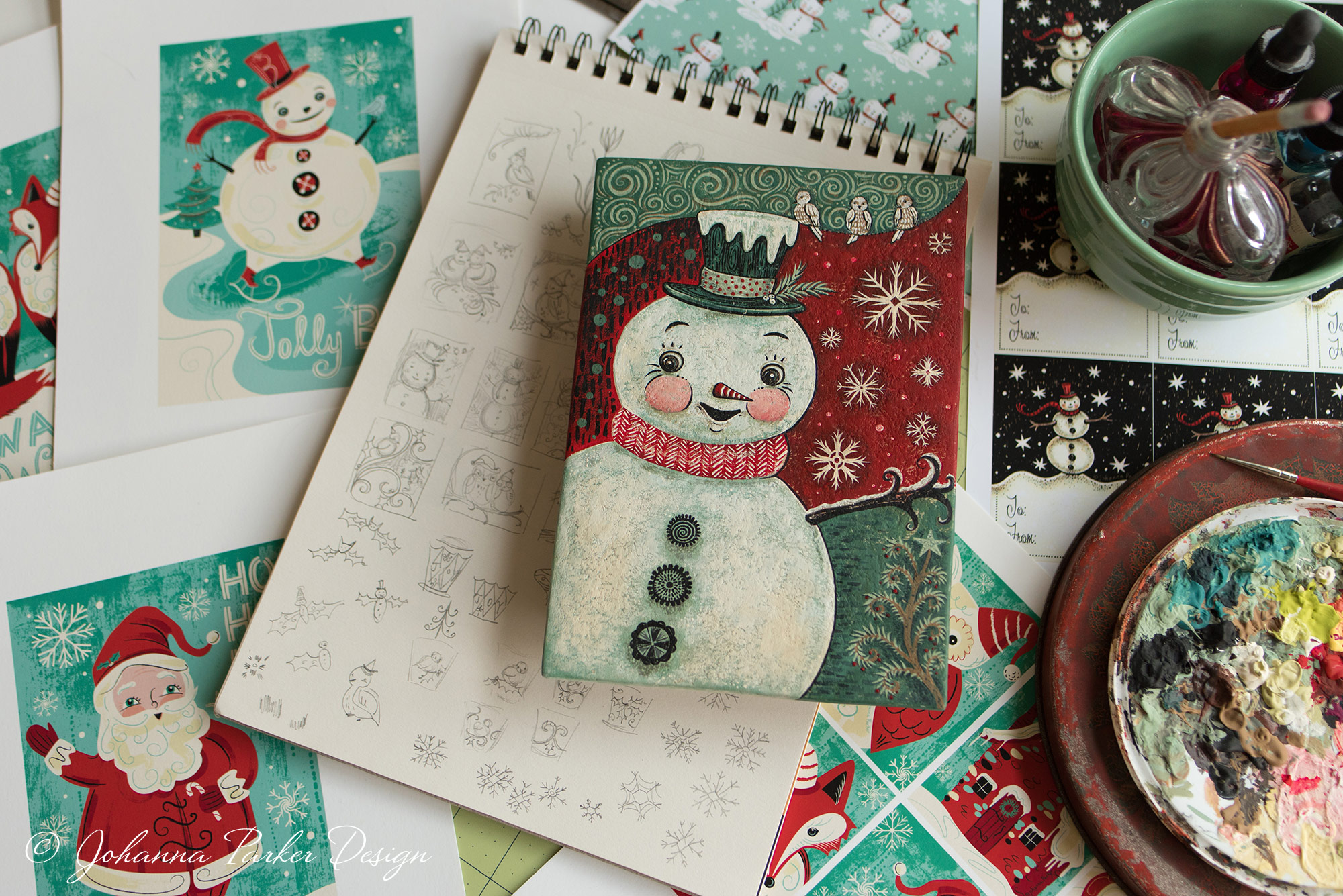 This vignette shows a snapshot of various holiday art projects all grouped together. It's a fun mix of my printed graphics, rough pencil sketches, a painted art panel, pattern repeats and illustrated gift tags ~ All a variety of designs that I could easily delve into on any given day!