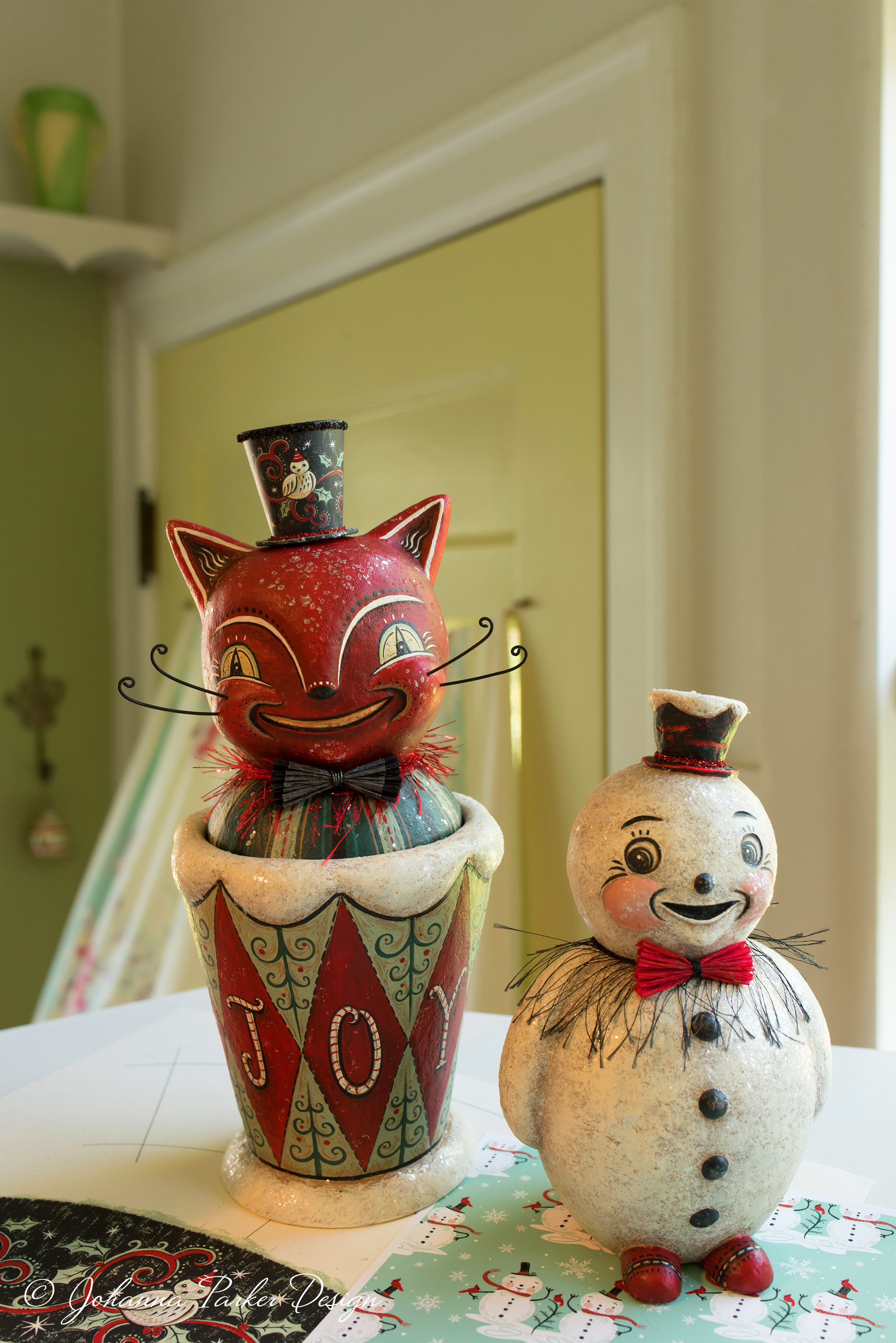 We chose this mischievous pair of holiday folk art characters, a rare,grinning red cat candy container and a standing snowman, to accompany me in my portrait.