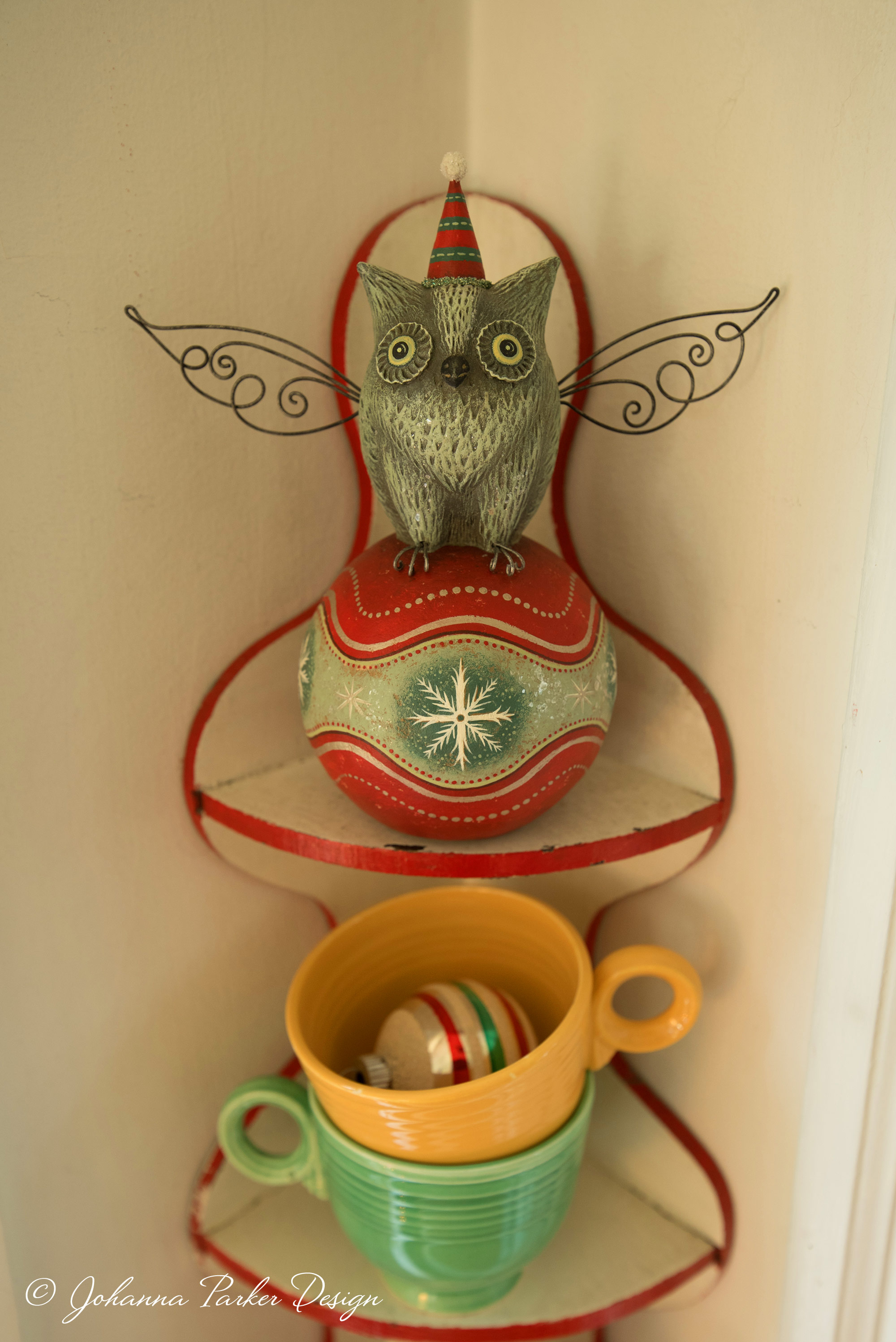 An original owl sculpture, perched atop a decorated ball, keeps watch over my studio space.