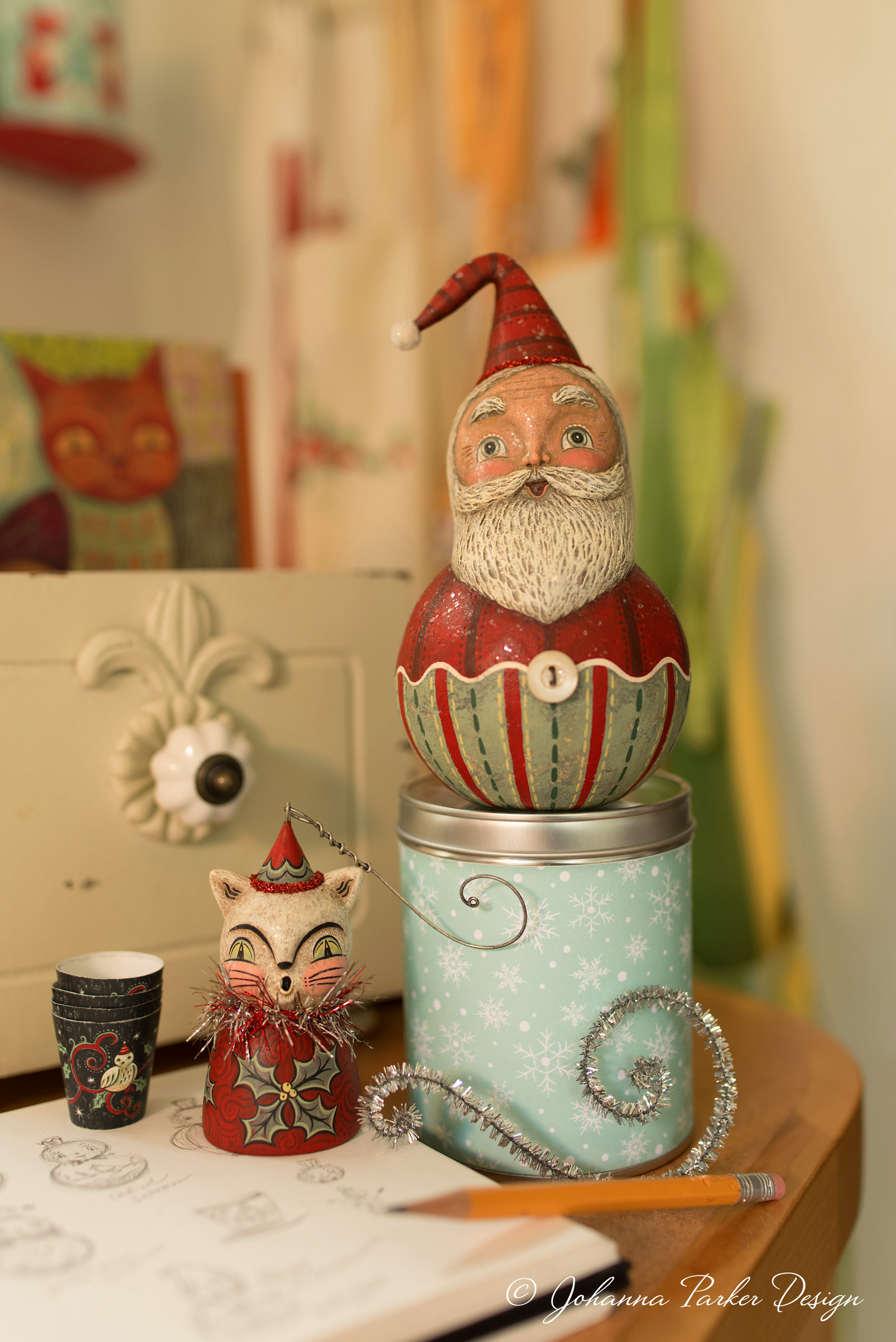 A wall nook of my hanging aprons creates a soft backdrop for my jolly ball-shaped Santa and winter kitty ornament bell.