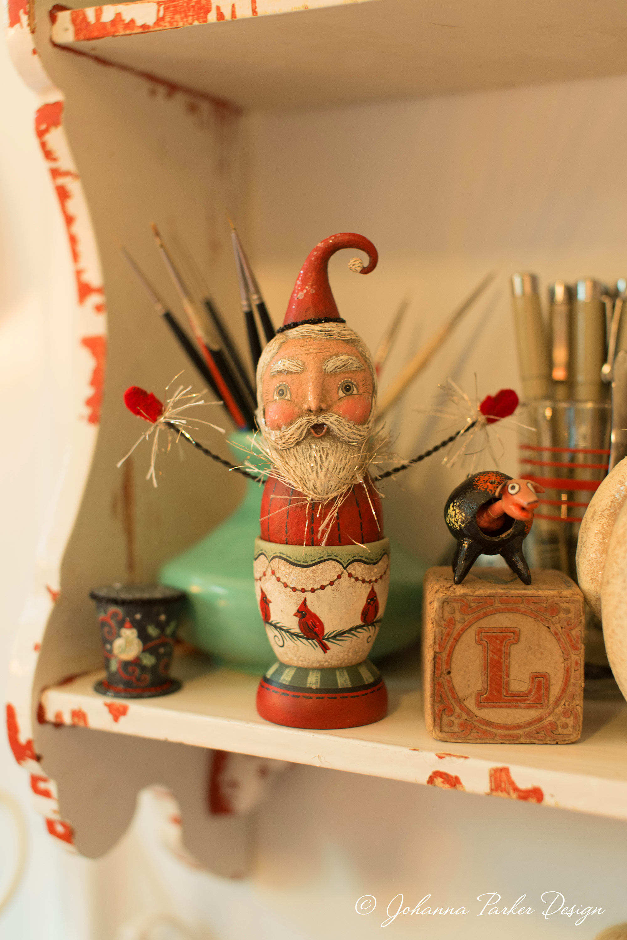 Paintbrushes and pens surround a sweet Santa egg cup character.