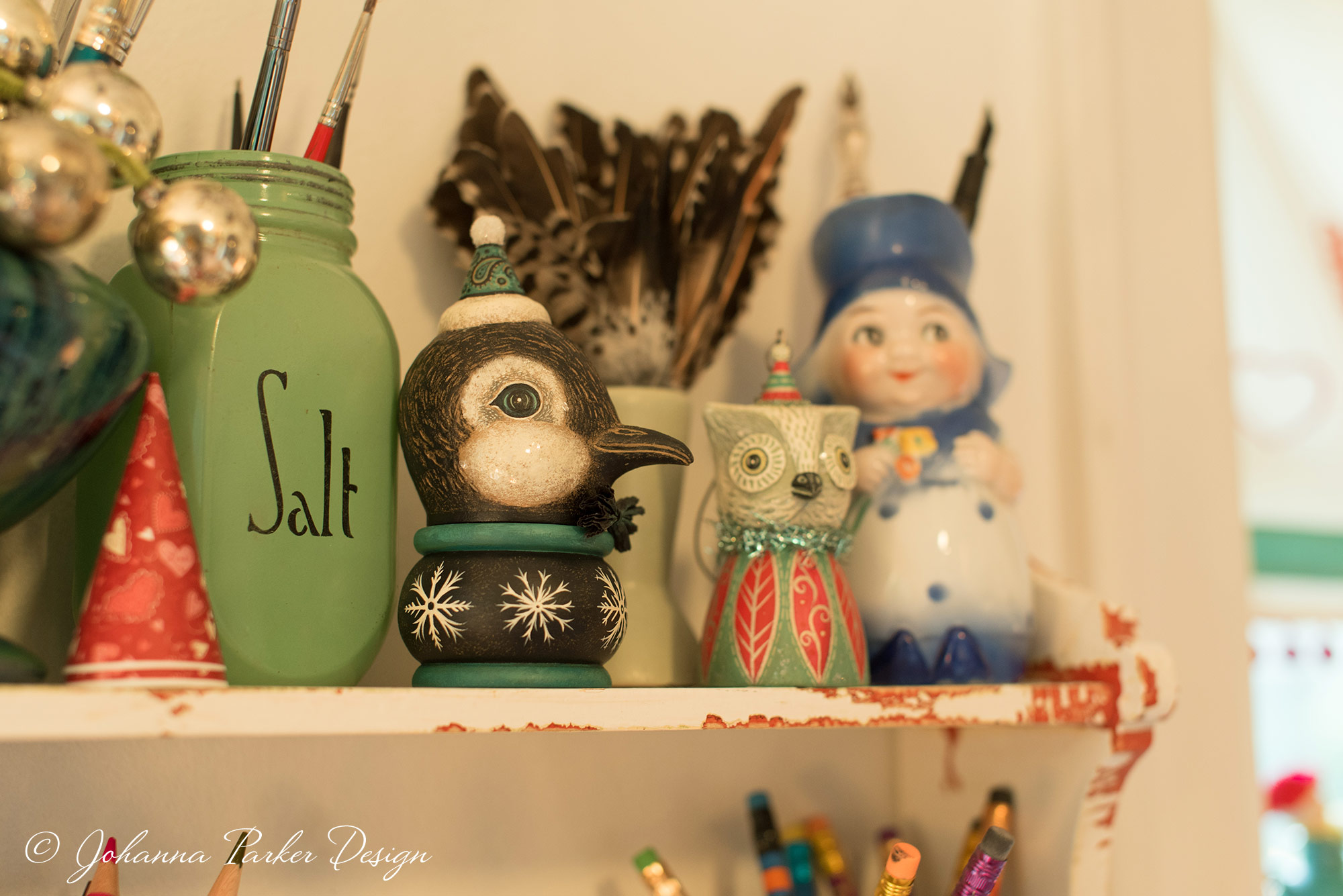A closer peek at my shelf reveals a sweet penguin kettle cup and an owl ornament bell. Everything from feathers to vintage pottery and glassware add functionality and design inspiration to where I sit to sculpt and paint.