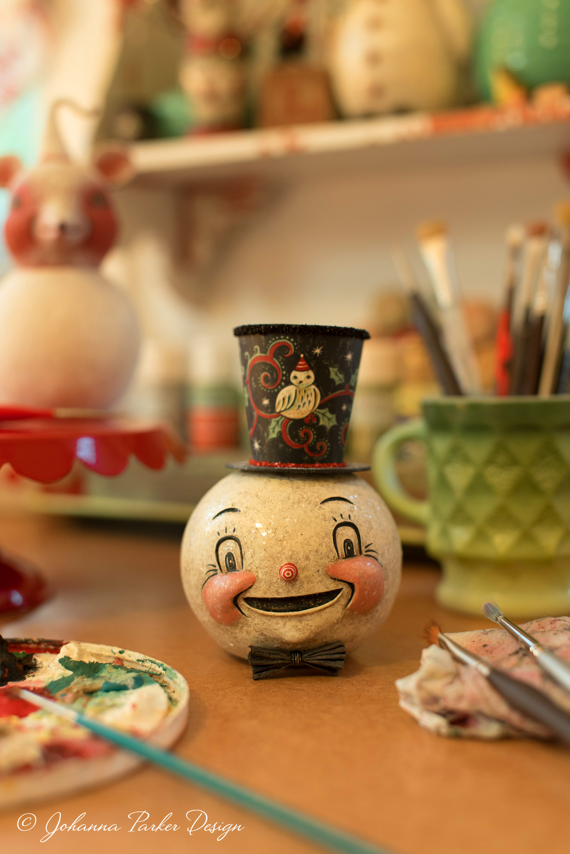 A jolly snowman head, donning an illustrated top hat, sports an enchanting smile.