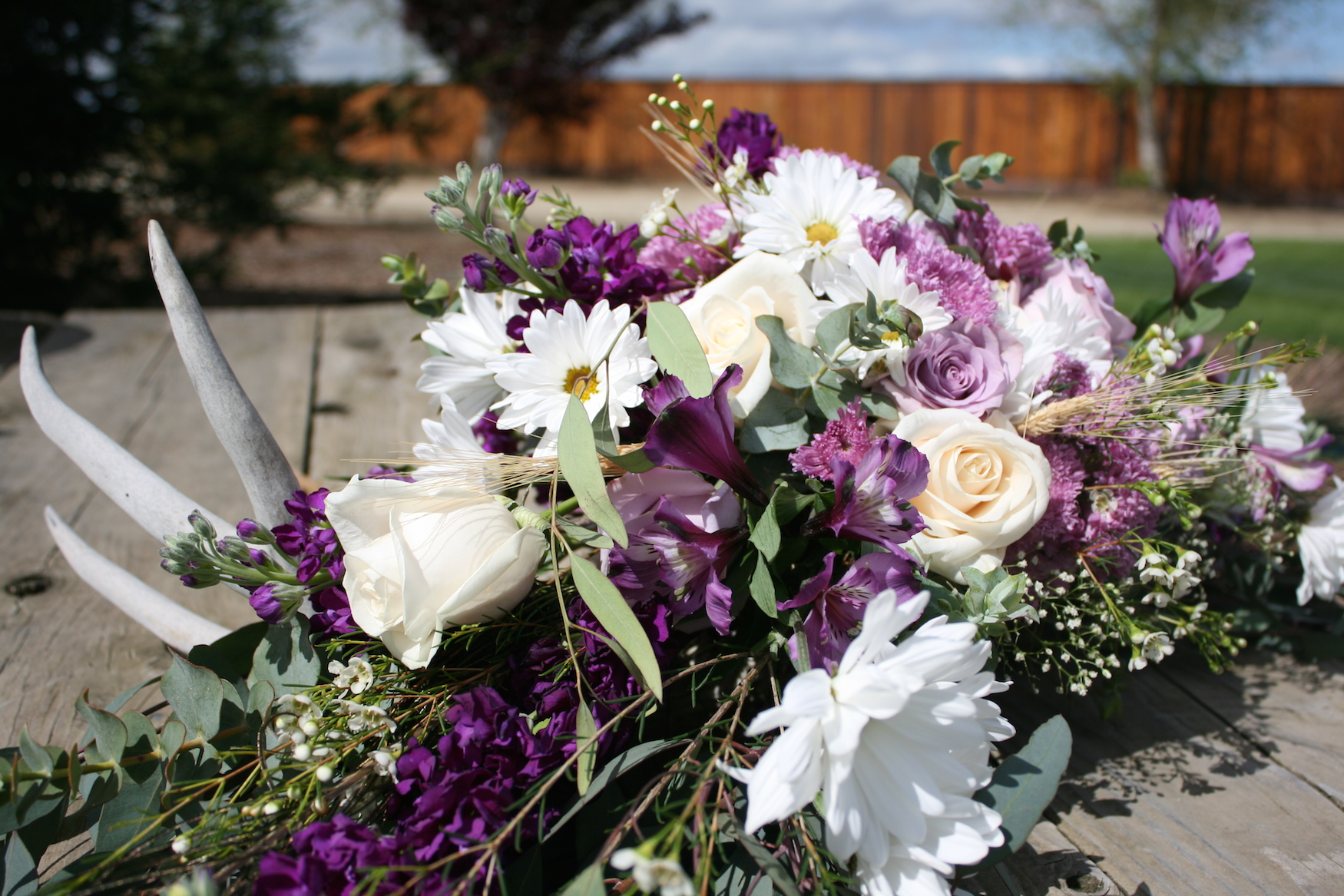 Feature piece floral arrangement with antler accent.