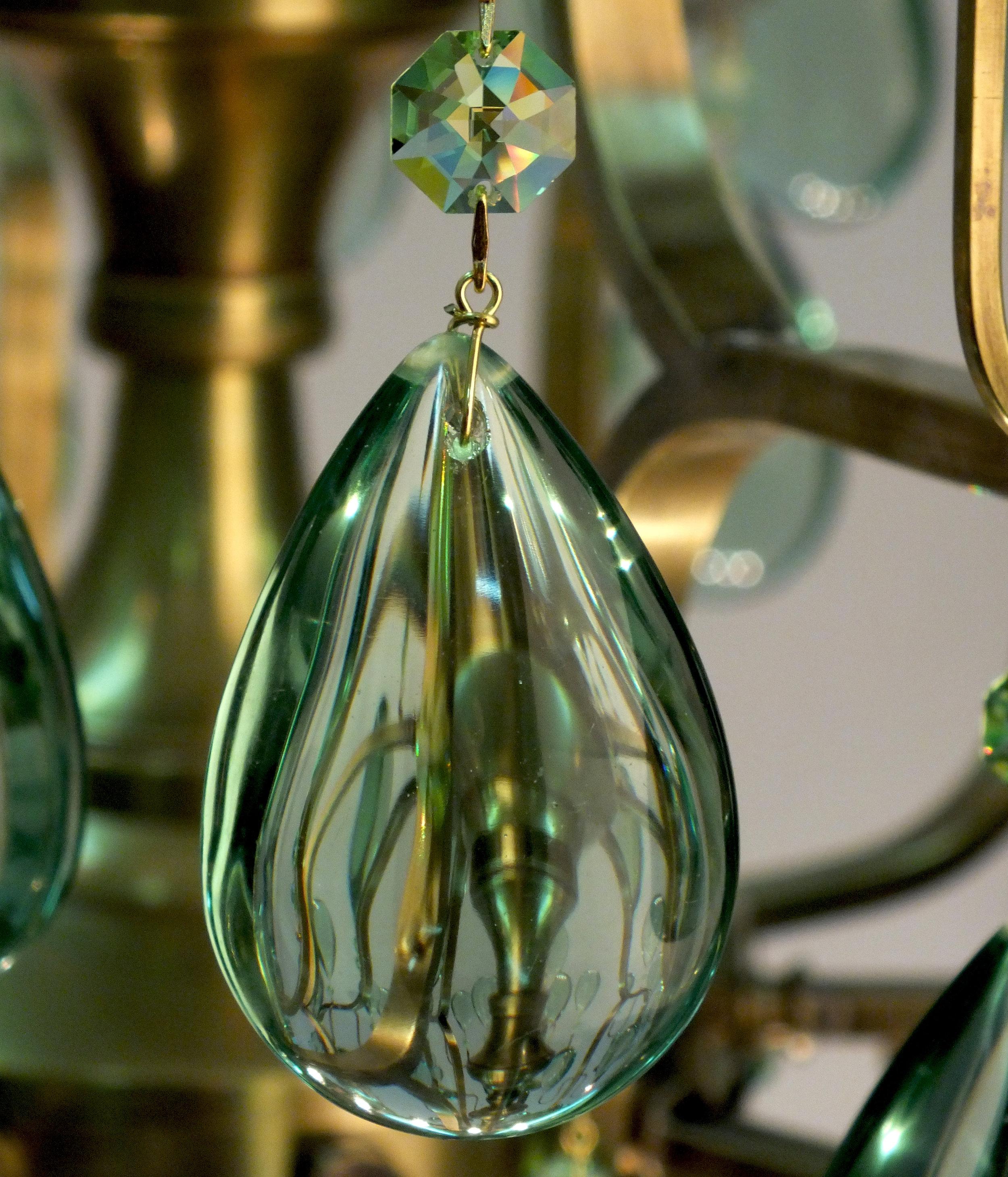 Foto de detalhe do Lustre Sevilha, com obsidianas verdes, cristais Light Peridot Swarovski e conectores entre os cristais banhados a Ouro 24K.