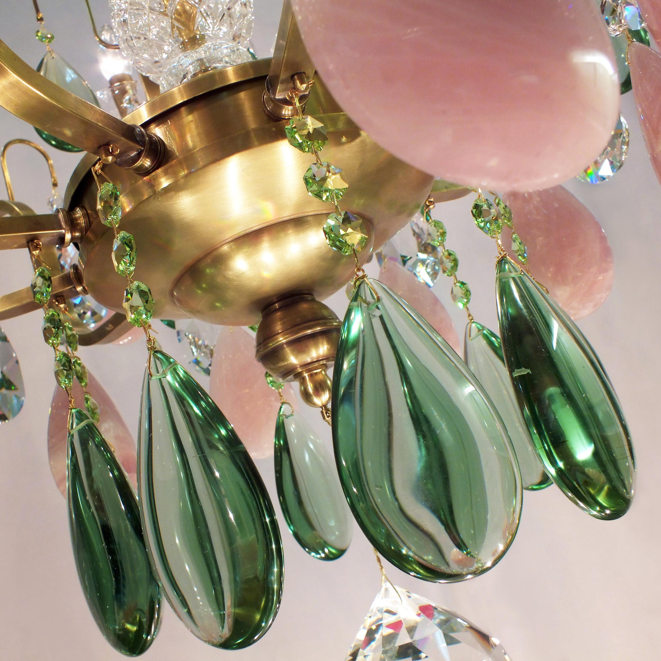 Foto de detalhe do Lustre Siena 10 braços, com obsidianas verdes, cristais de rocha rosa, cristais Light Peridot Swarovski e conectores entre os cristais banhados a Ouro 24K.