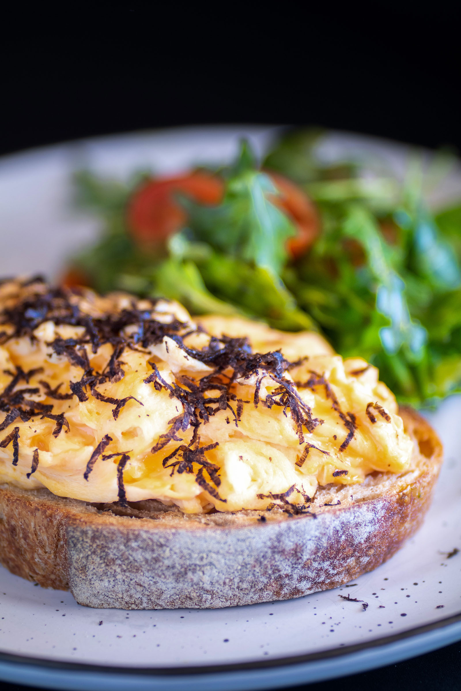 TruffleScrambled Eggs - Creamy scrambled free-range eggs, served atop a slice of toasted sourdough from Baker et Chef and accompanied with a colourful rocket and cherry tomato salad. Finished with fresh, fine shavings of the rich, locally-grown Manjimup black truffle.