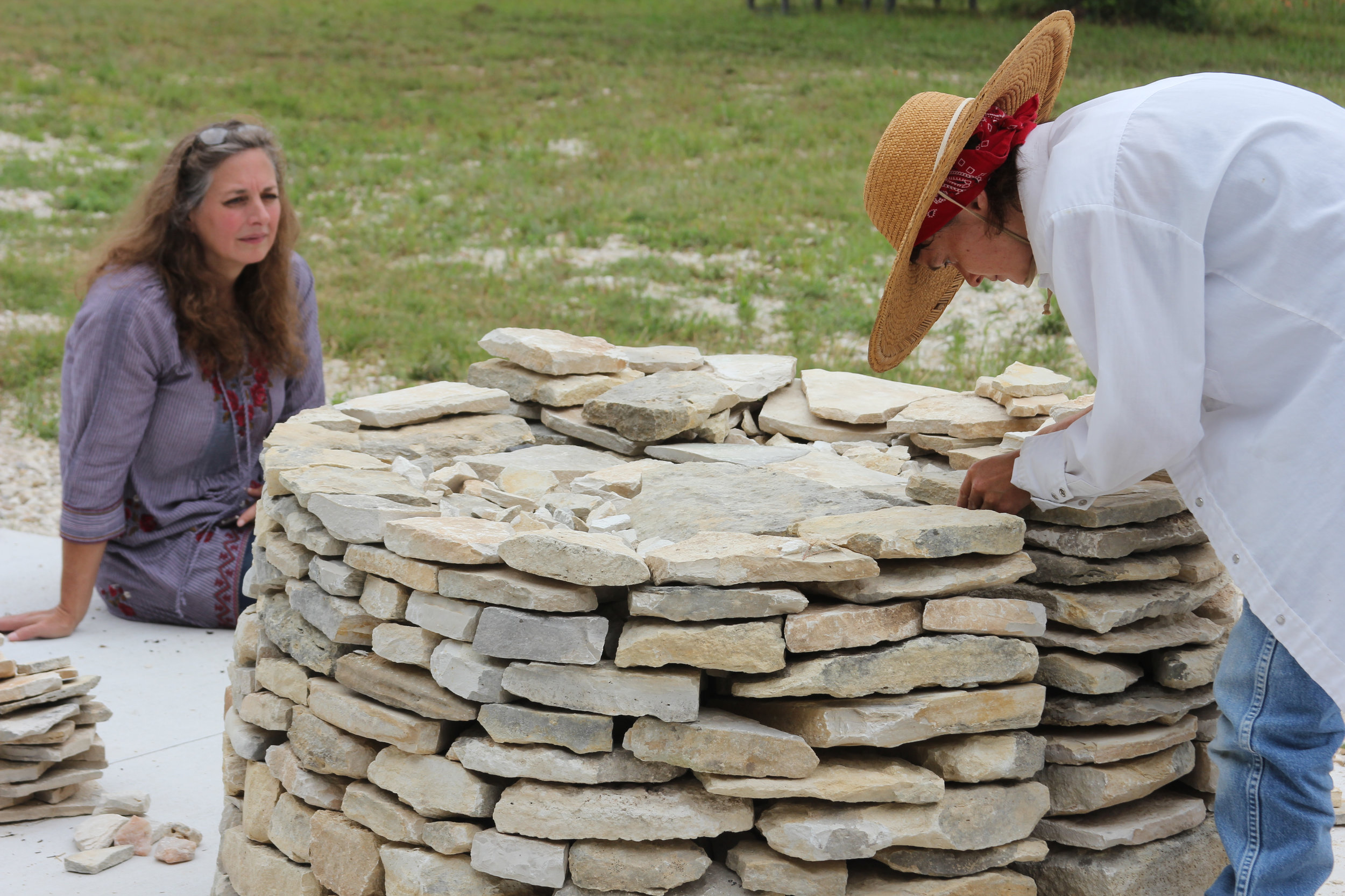 "Cheryl Quallenberg, director of the  Llano Earth Art Fest , home of the World Rock Stacking Championship, watches Katy carefully place limestone and pre-cambrain rock pieces to build her sculpture, ""Filter"" at MUSEOBENINI."