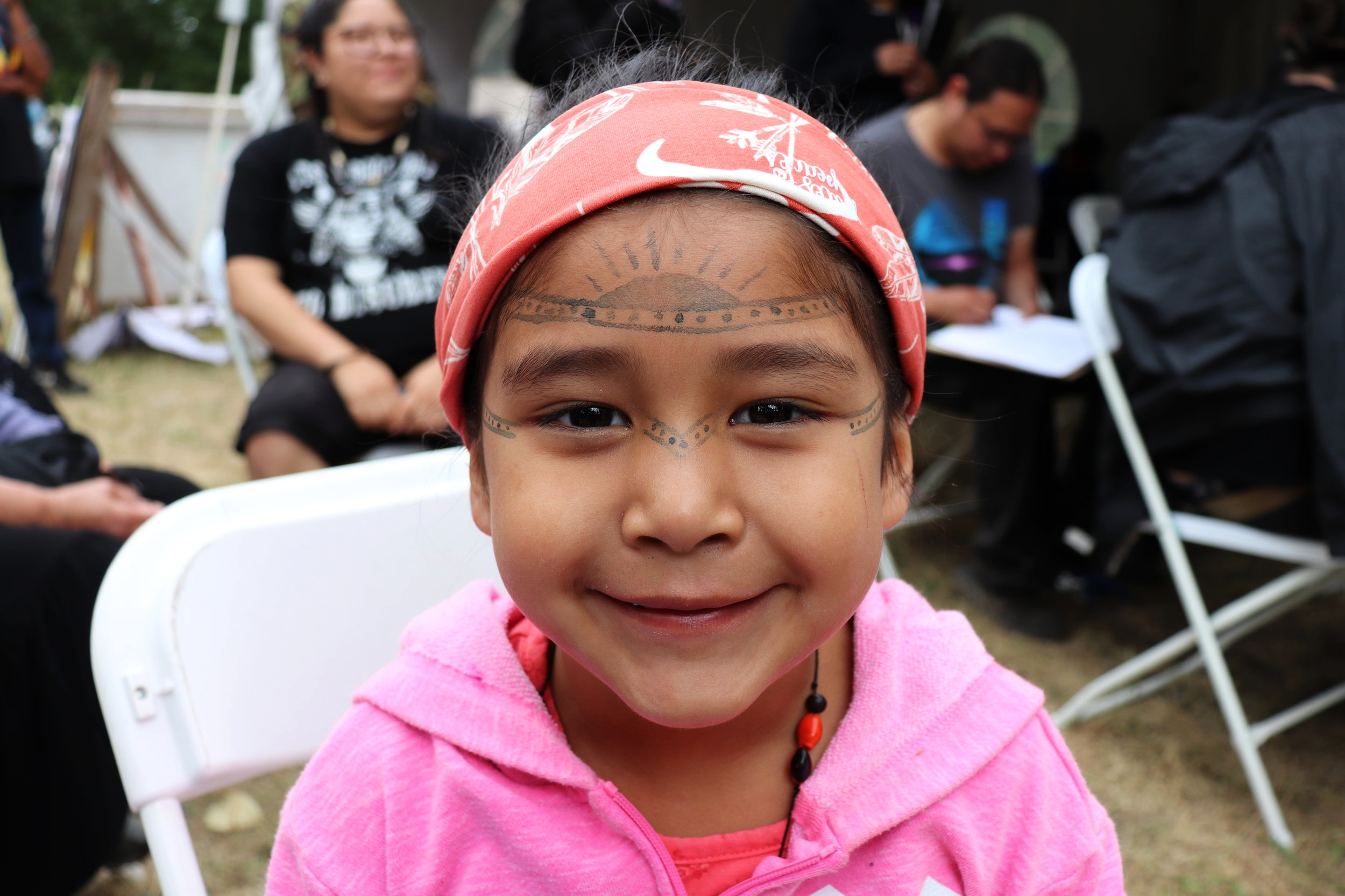 Young girl gets painted by member of the Federation of the Huni Kui tribe of the Brazilian Amazon rainforest.