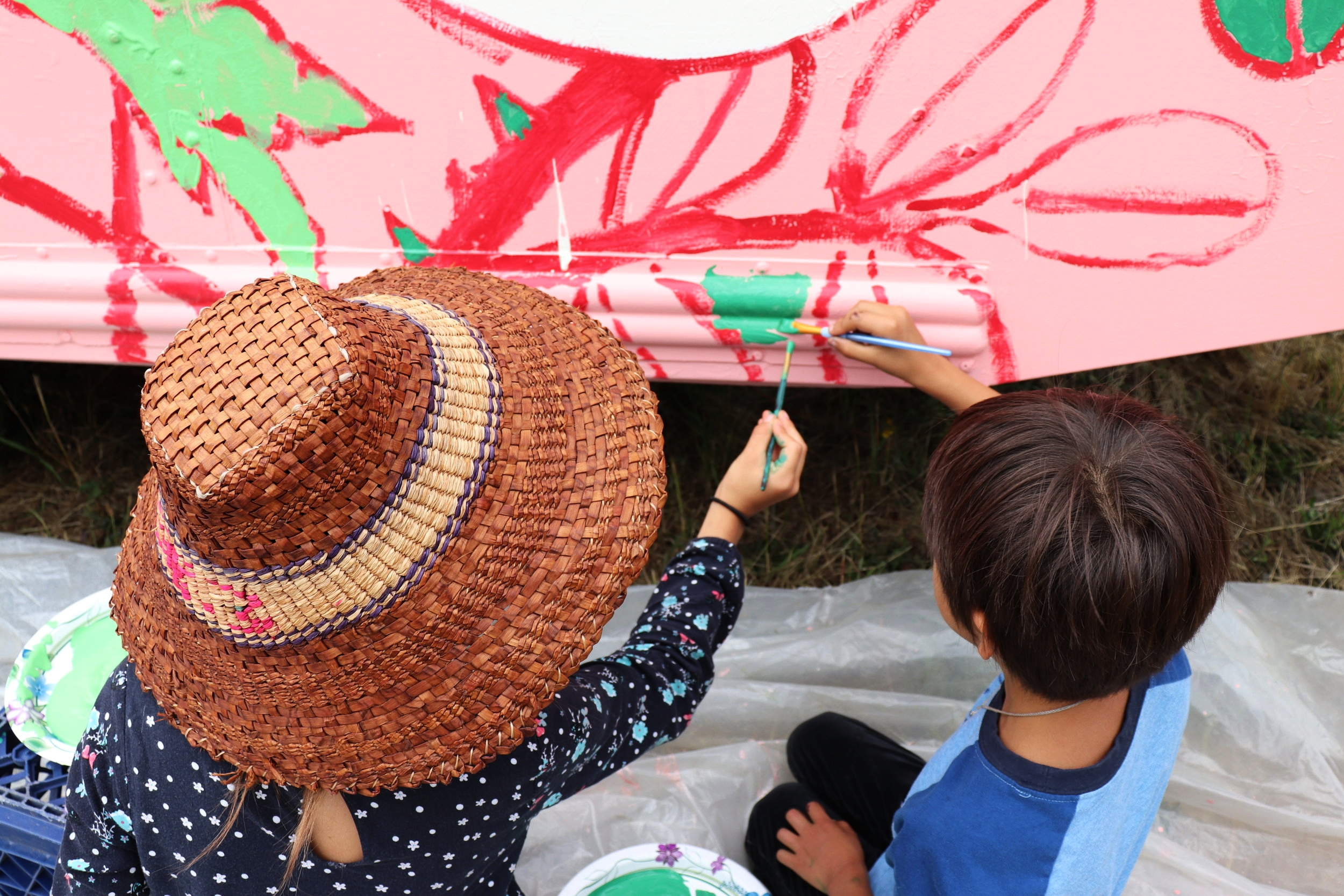 Youth paint the Canoe Journey Herbalists' bus.