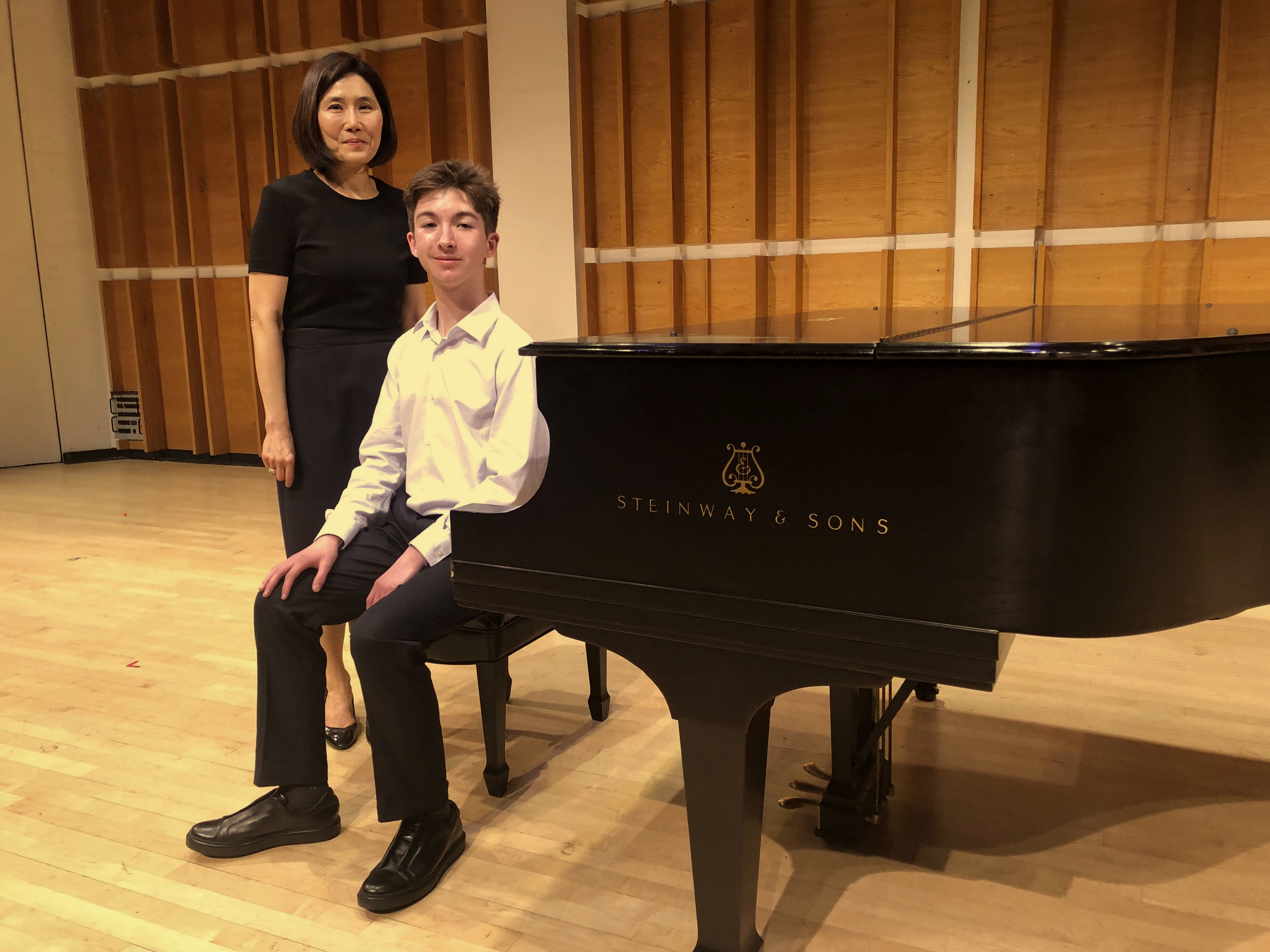 Sebastian on stage with Dr. Rosa Parks at the International Grande Music Competition